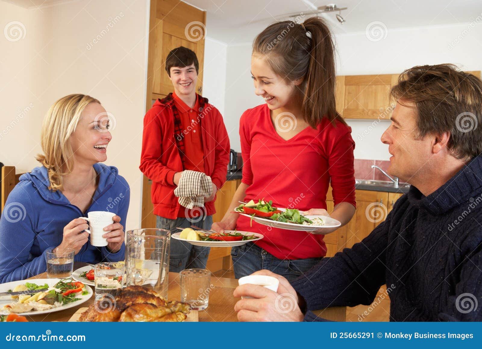 Enfants d adolescent utiles servant la nourriture aux parents