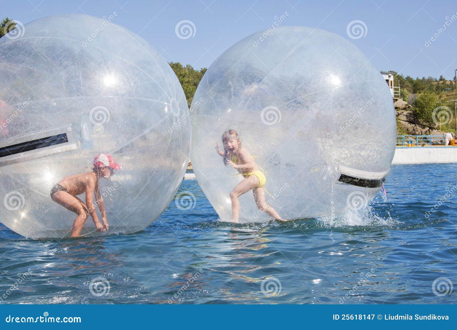 enfants dans un ballon flottant sur l 39 eau photographie. Black Bedroom Furniture Sets. Home Design Ideas