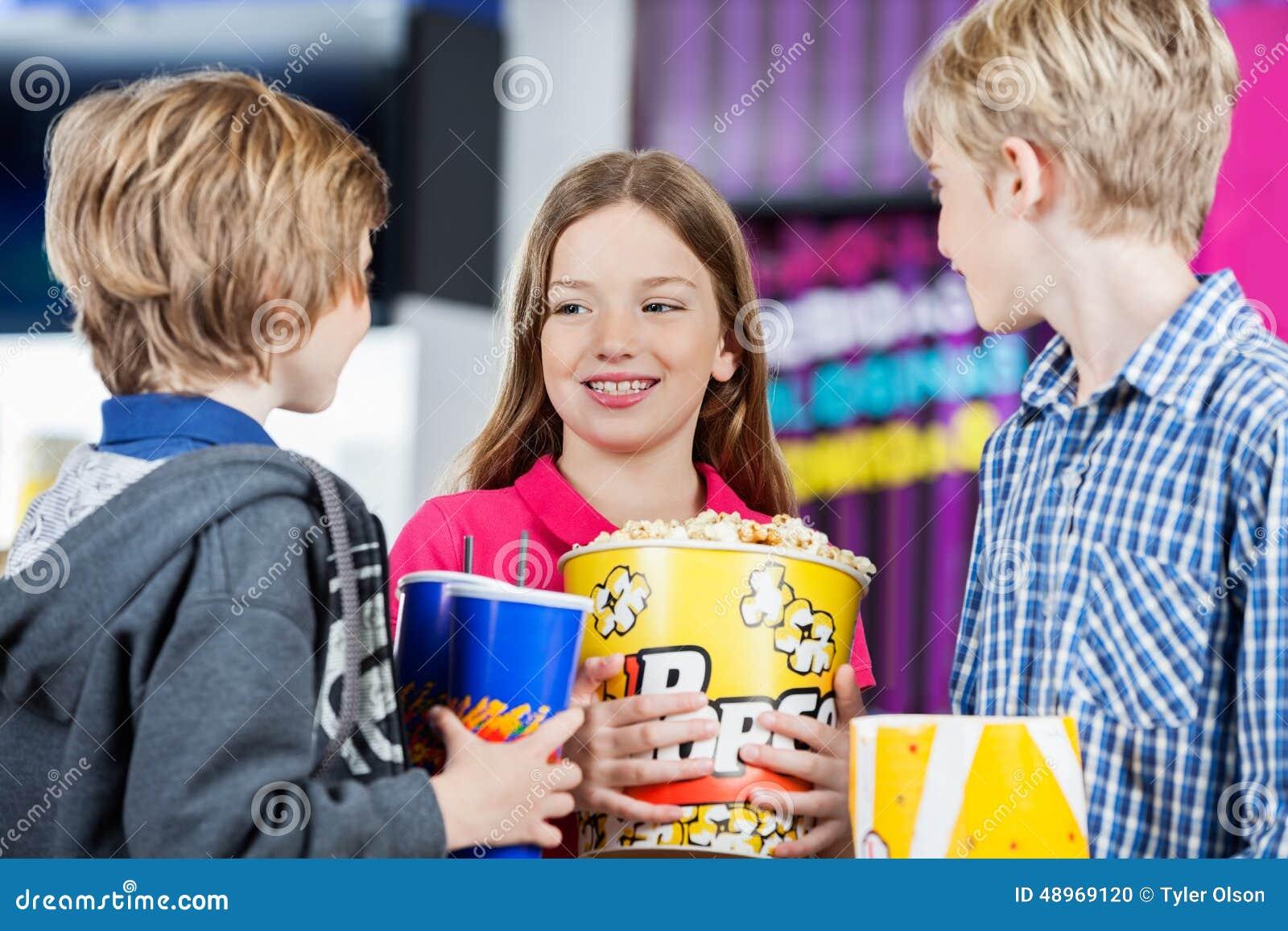Enfants de mêmes parents conversant tout en tenant des casse-croûte au cinéma