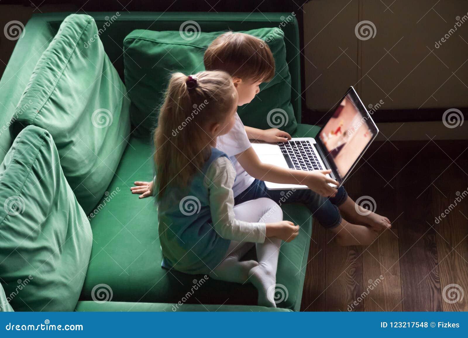 Enfants de mêmes parents garçon et bandes dessinées de observation d enfant de fille utilisant le togethe d ordinateur portable