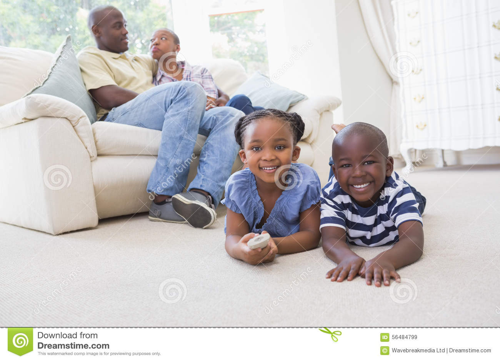 Enfants de mêmes parents heureux s asseyant à la télévision de observation de plancher
