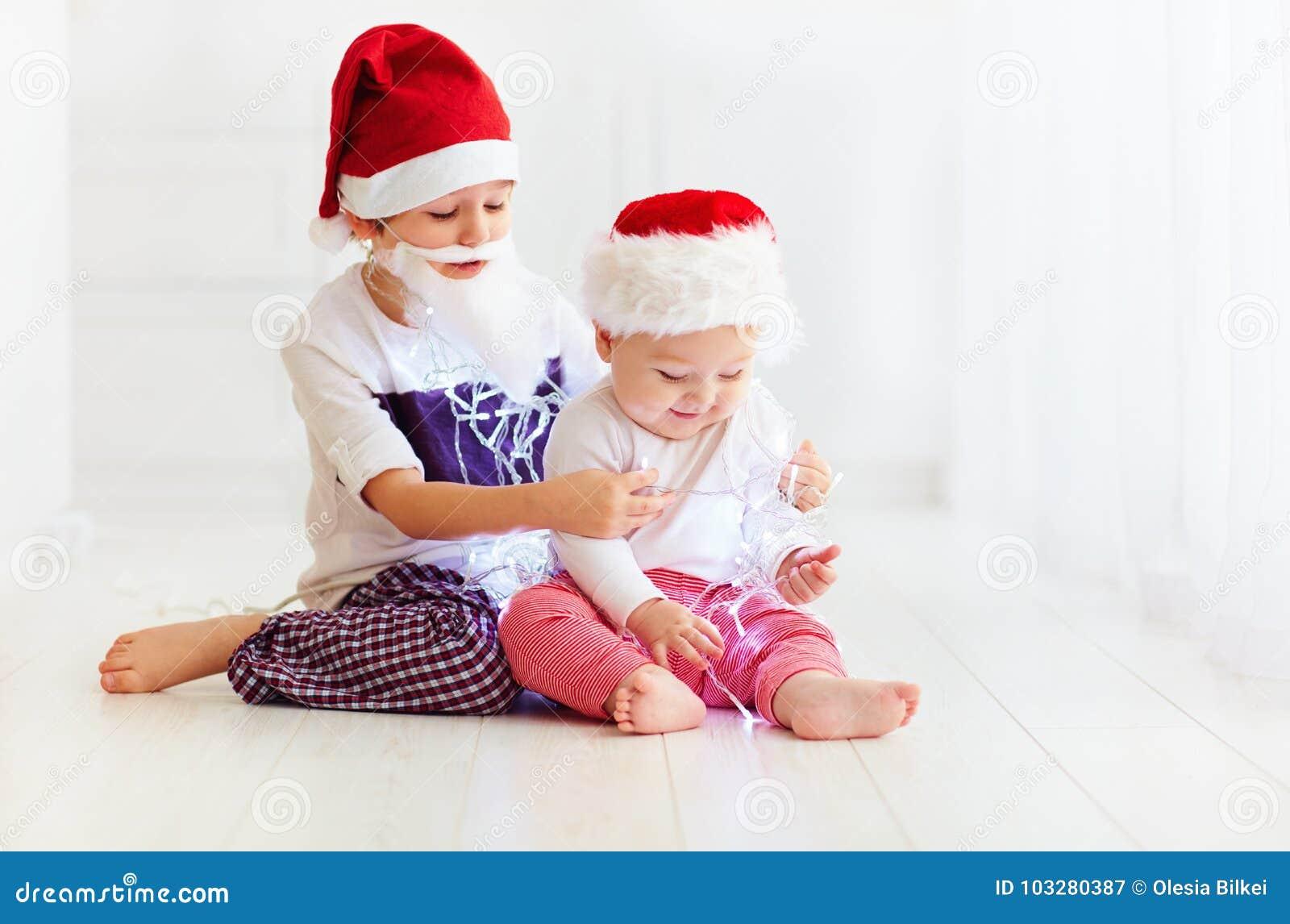 Enfants de mêmes parents mignons de frère, enfants dans des chapeaux du ` s de Santa et guirlande jouant à la maison