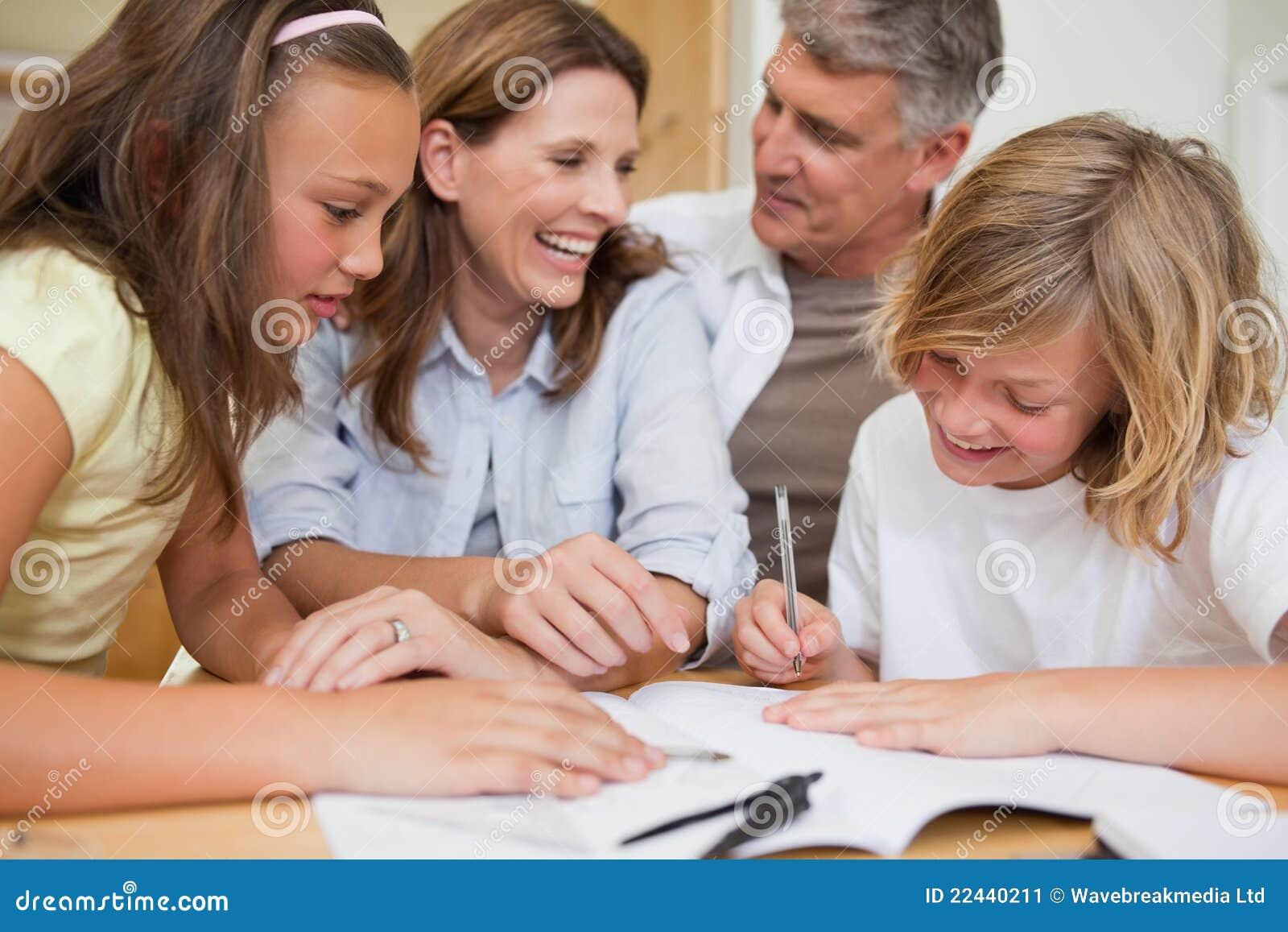Enfants de mêmes parents obtenant l aide avec des devoirs des parents