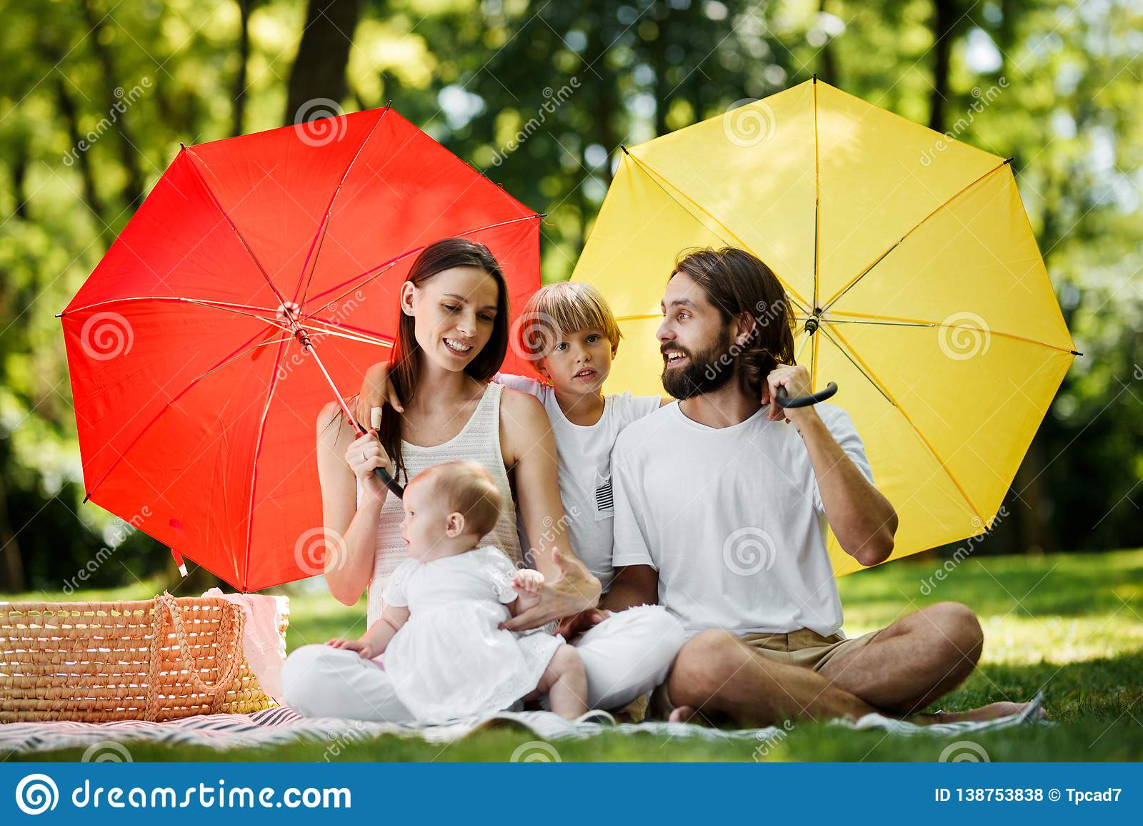 Enfants drôles avec la maman et le papa s asseyant sur la couverture sous les grands parapluies rouges et jaunes les couvrant du