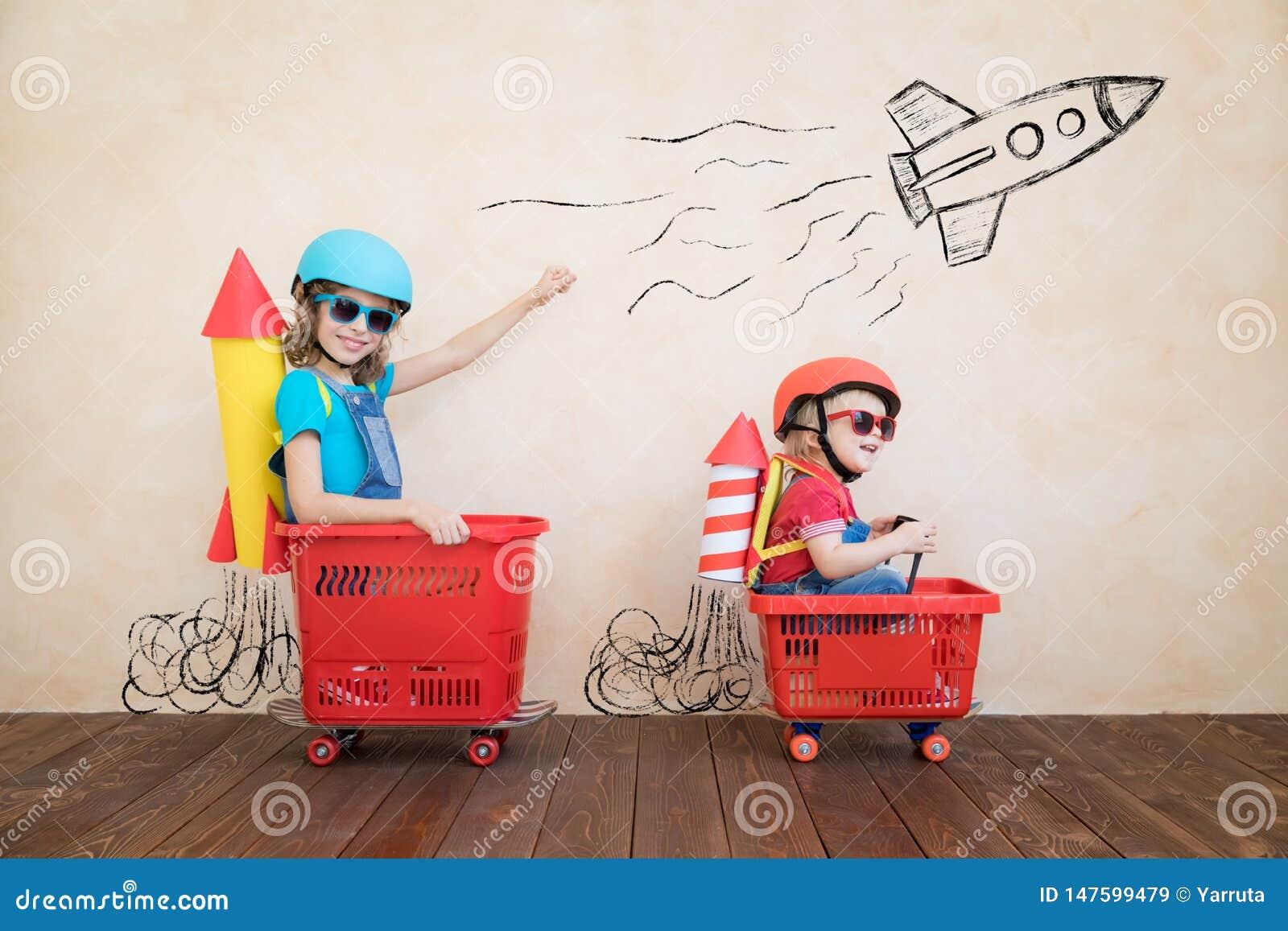 Enfants dr?les conduisant la voiture de jouet d int?rieur