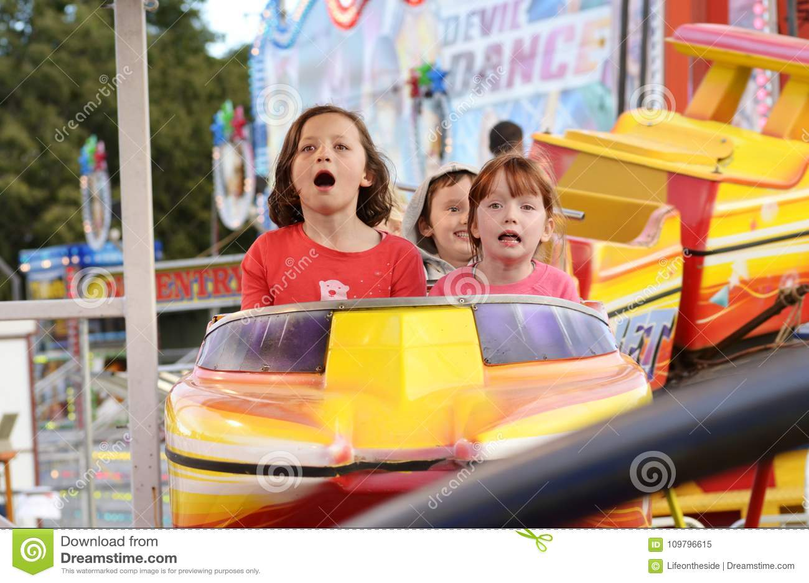 Enfants enthousiastes criant sur le tour de montagnes russes de carnaval