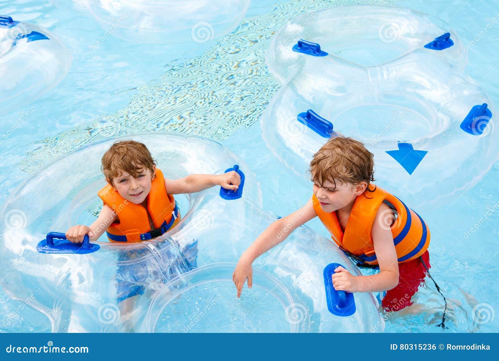 Enfants enthousiastes dans l équitation de parc aquatique sur la glissière avec le flotteur