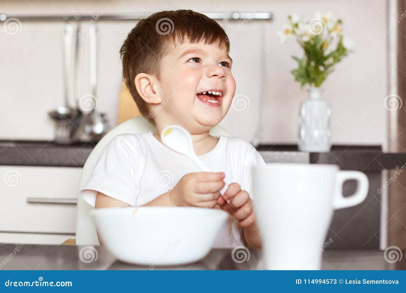 Enfants et concept de nutrition Le petit enfant mignon avec plaisir de sourire mange des céréales savoureuses et boit du thé, éta