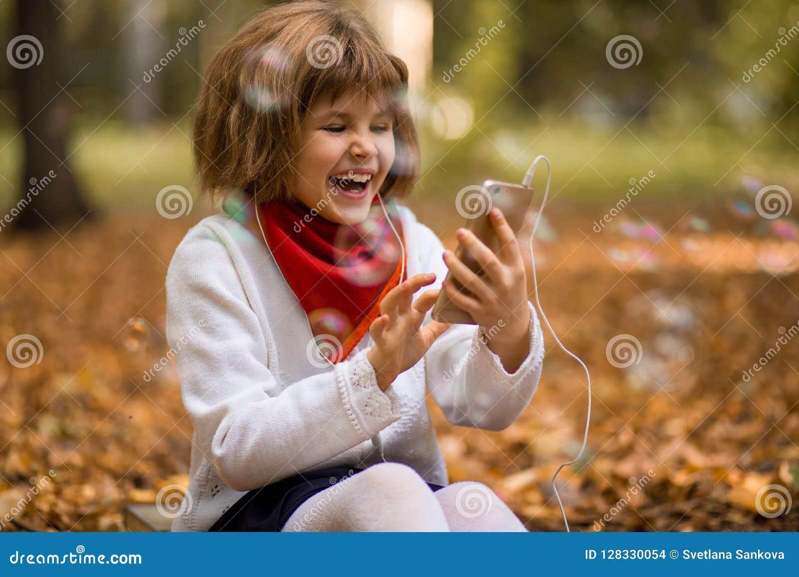 Enfants et concept de technologie - fille avec le smartphone ayant l appel visuel