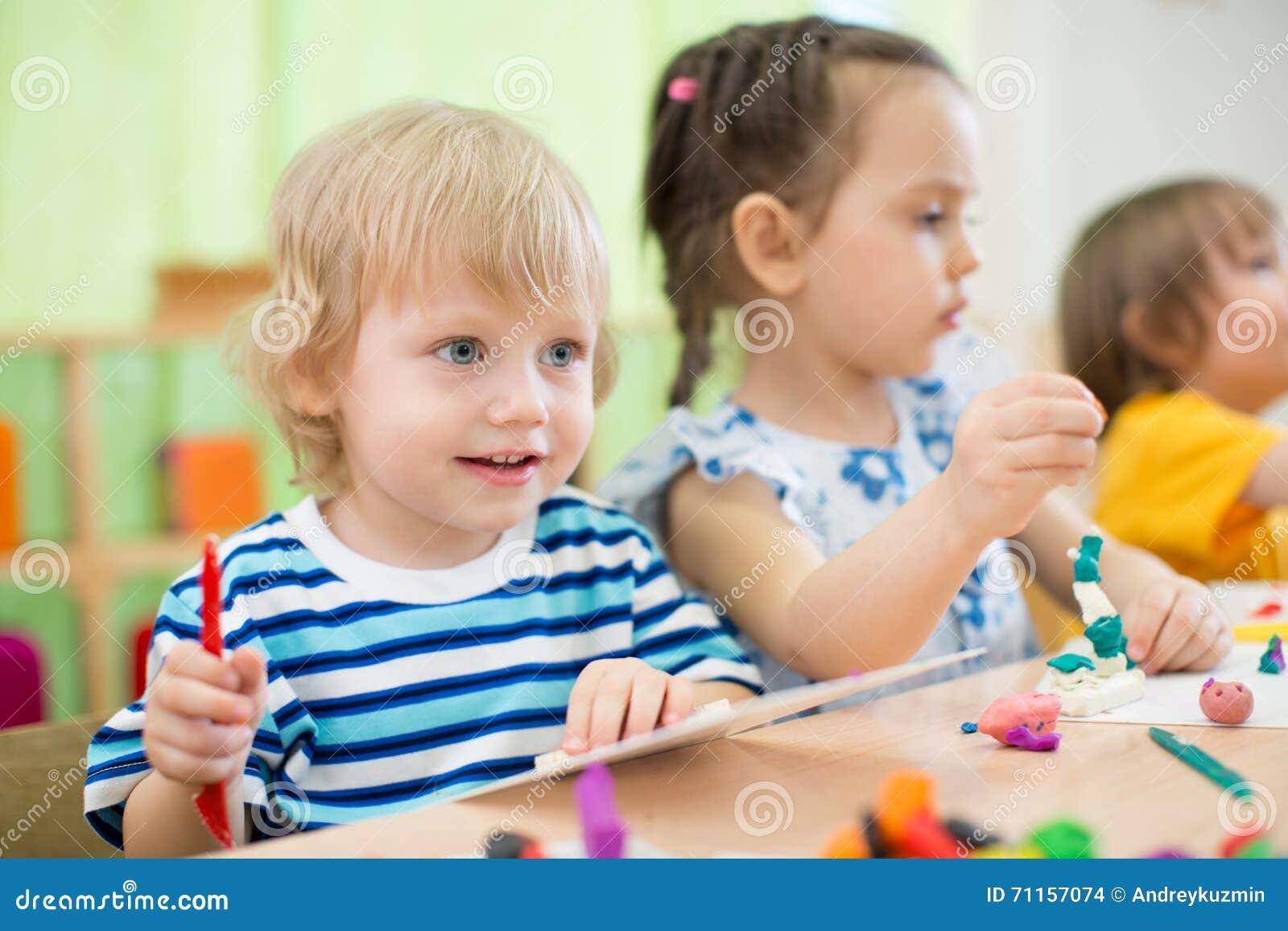 Enfants faisant des arts et des métiers au centre de soins de jour ensemble