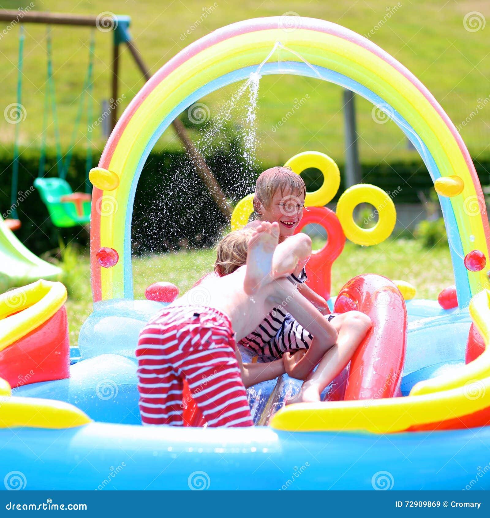 Enfants heureux éclaboussant dans la piscine gonflable de jardin