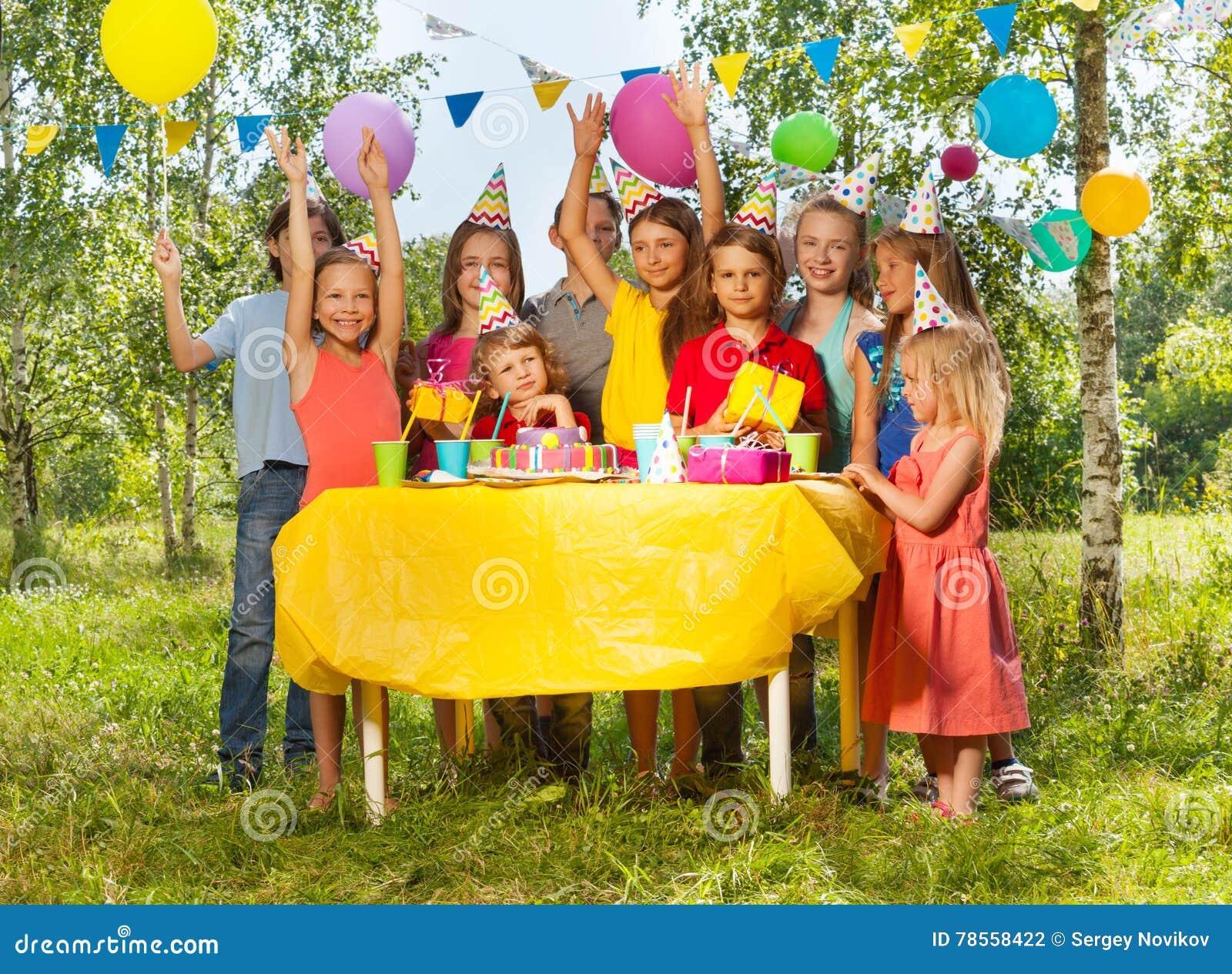 Enfants heureux ayant l amusement à la fête d anniversaire extérieure