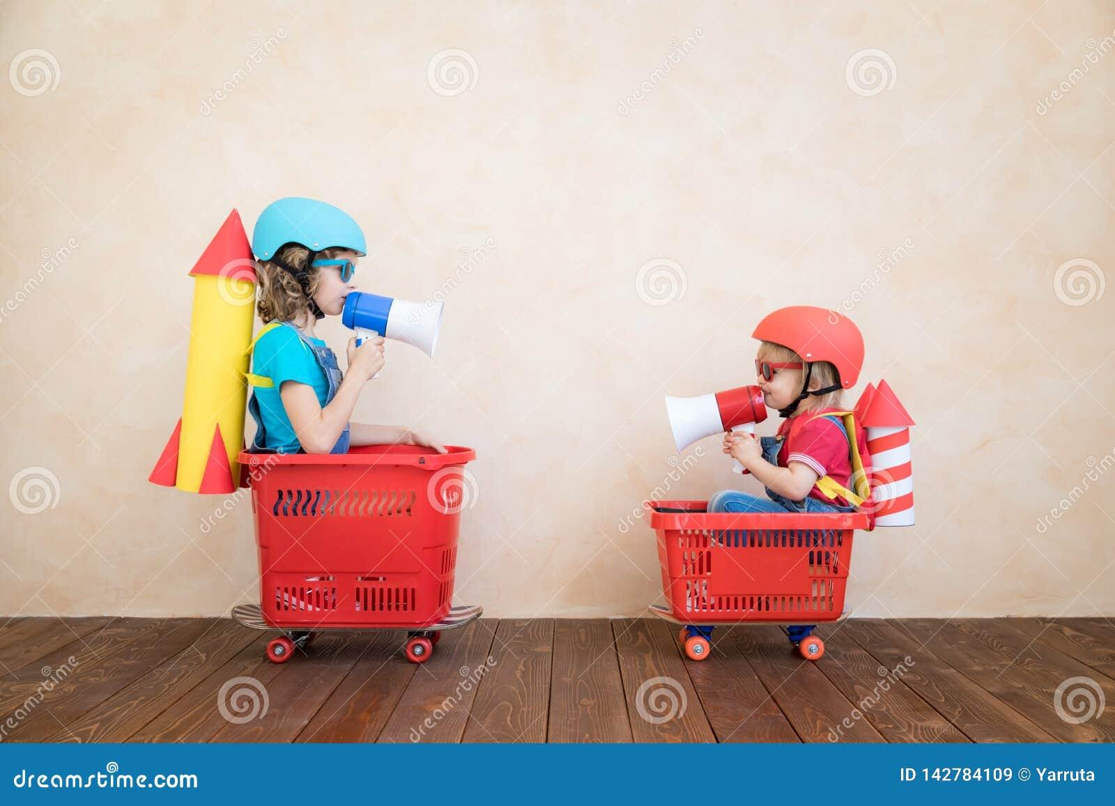 Enfants heureux conduisant la voiture de jouet à la maison