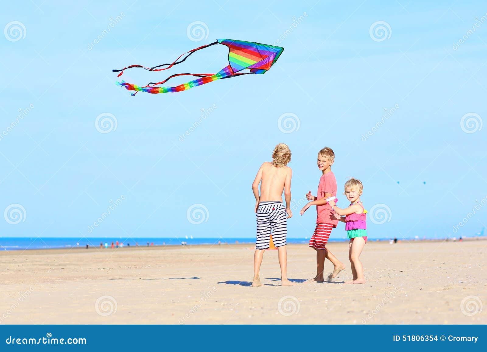 enfants heureux pilotant le cerf volant sur la plage photo. Black Bedroom Furniture Sets. Home Design Ideas