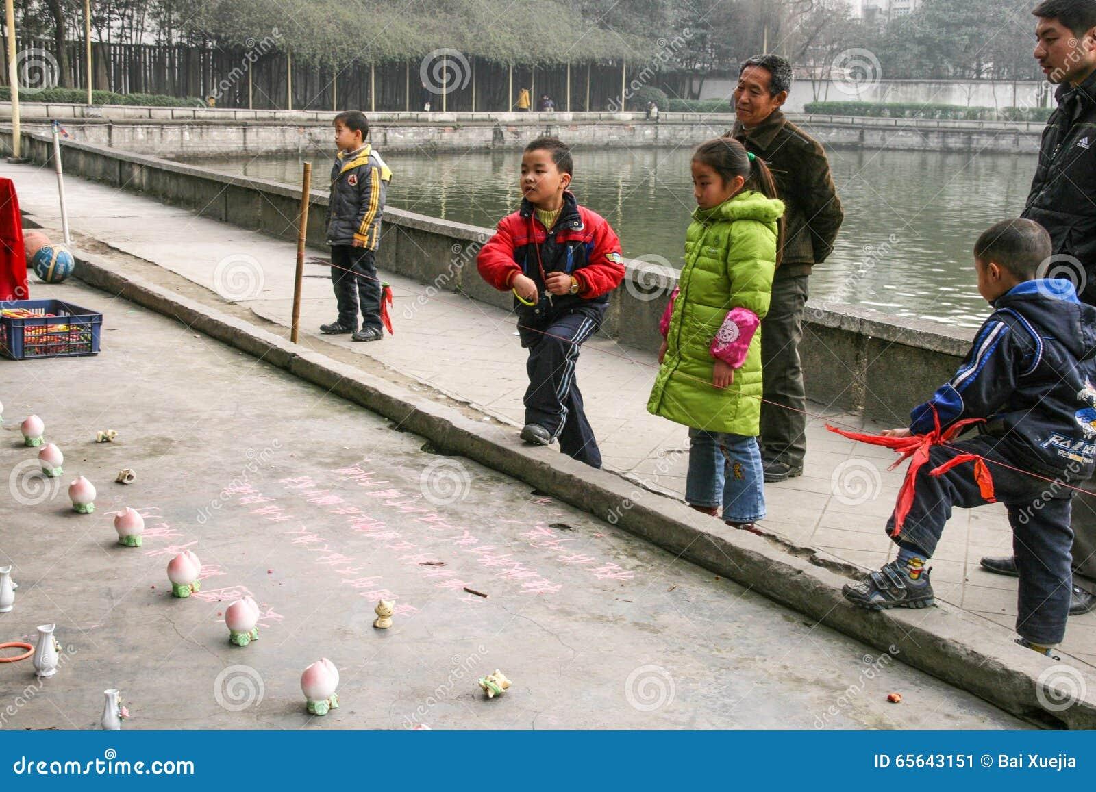 Enfants jetant des anneaux en parc de chengfei, Chengdu, porcelaine