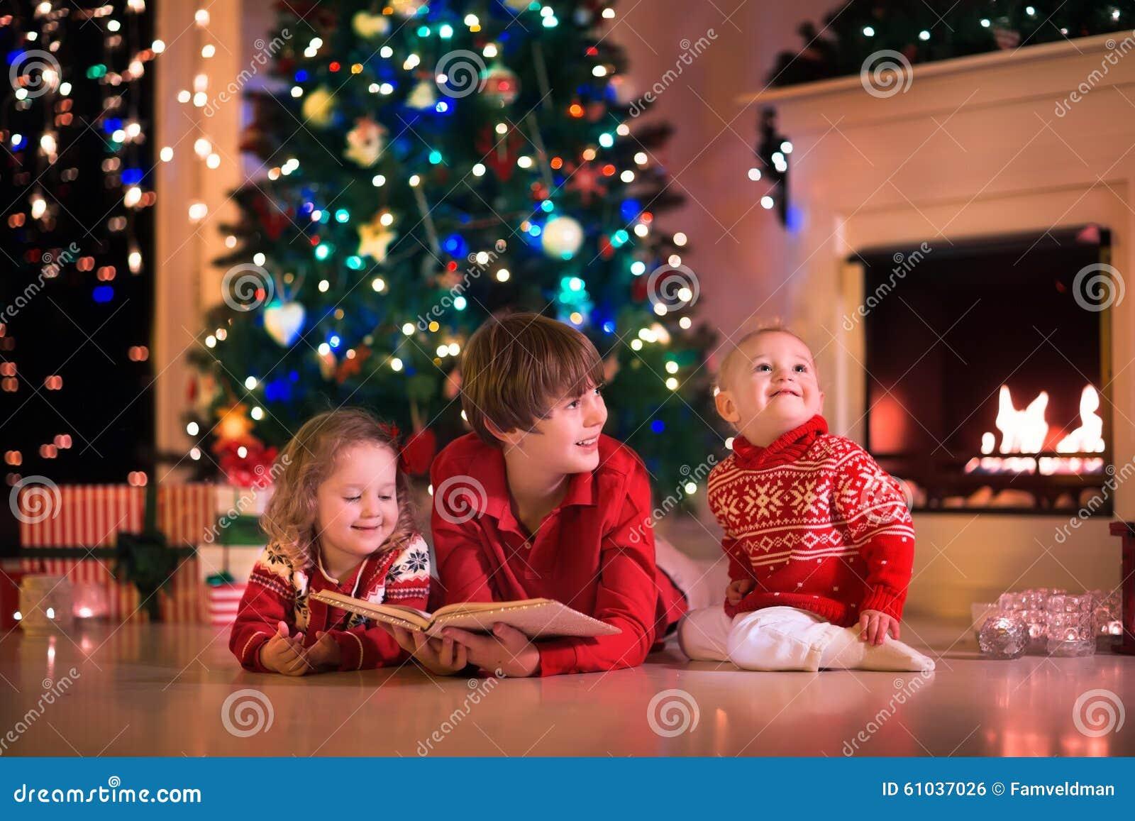 Enfants jouant à la cheminée le réveillon de Noël
