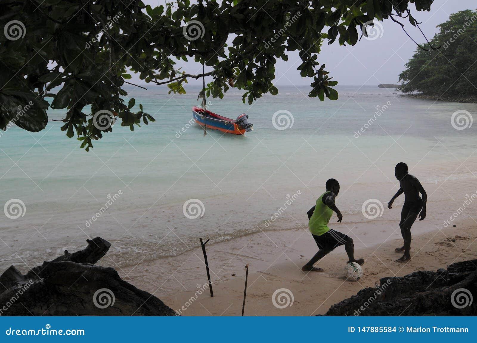 Enfants jouant au football à la plage de Winnifred