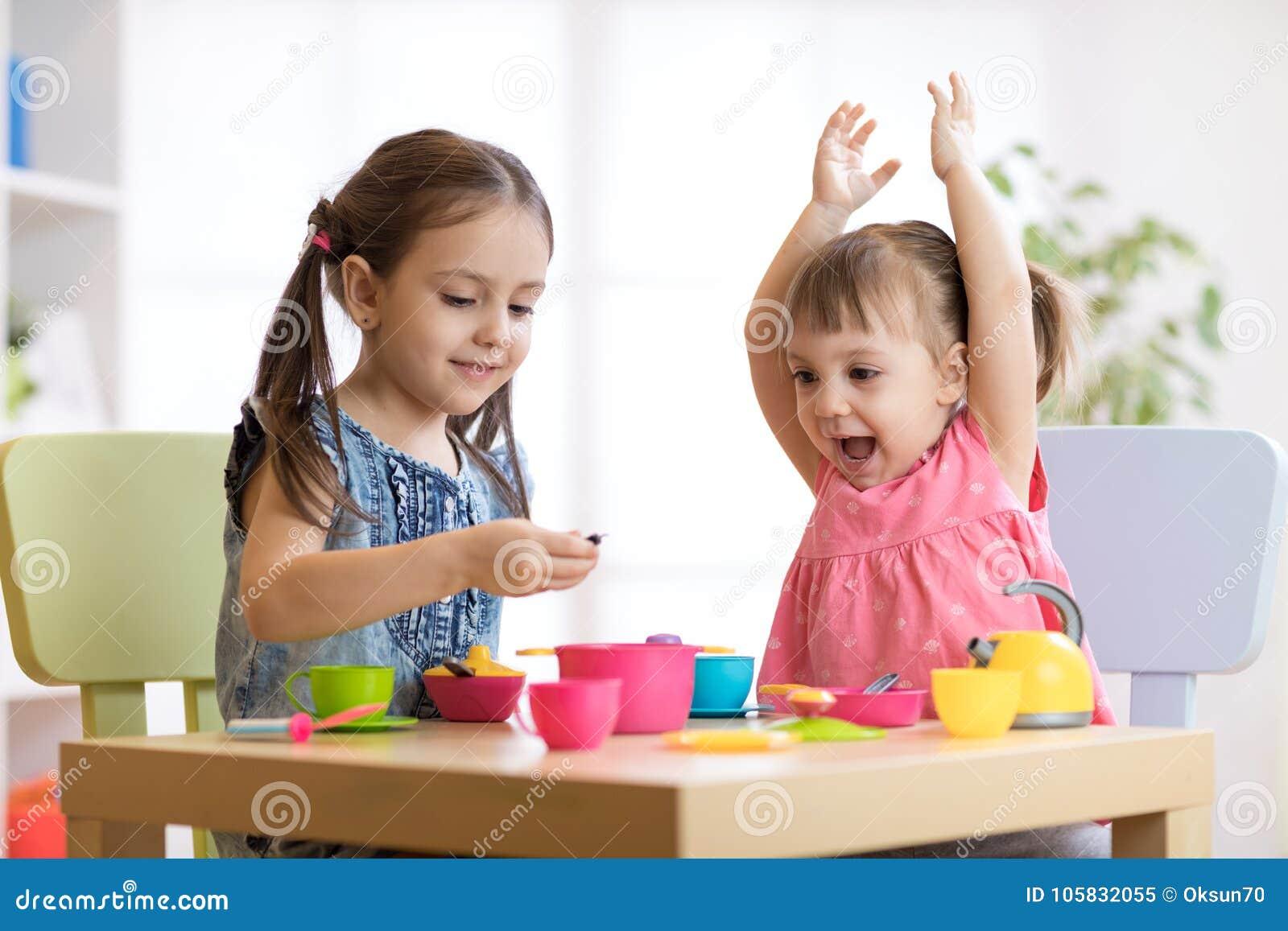 Enfants jouant avec la vaisselle en plastique