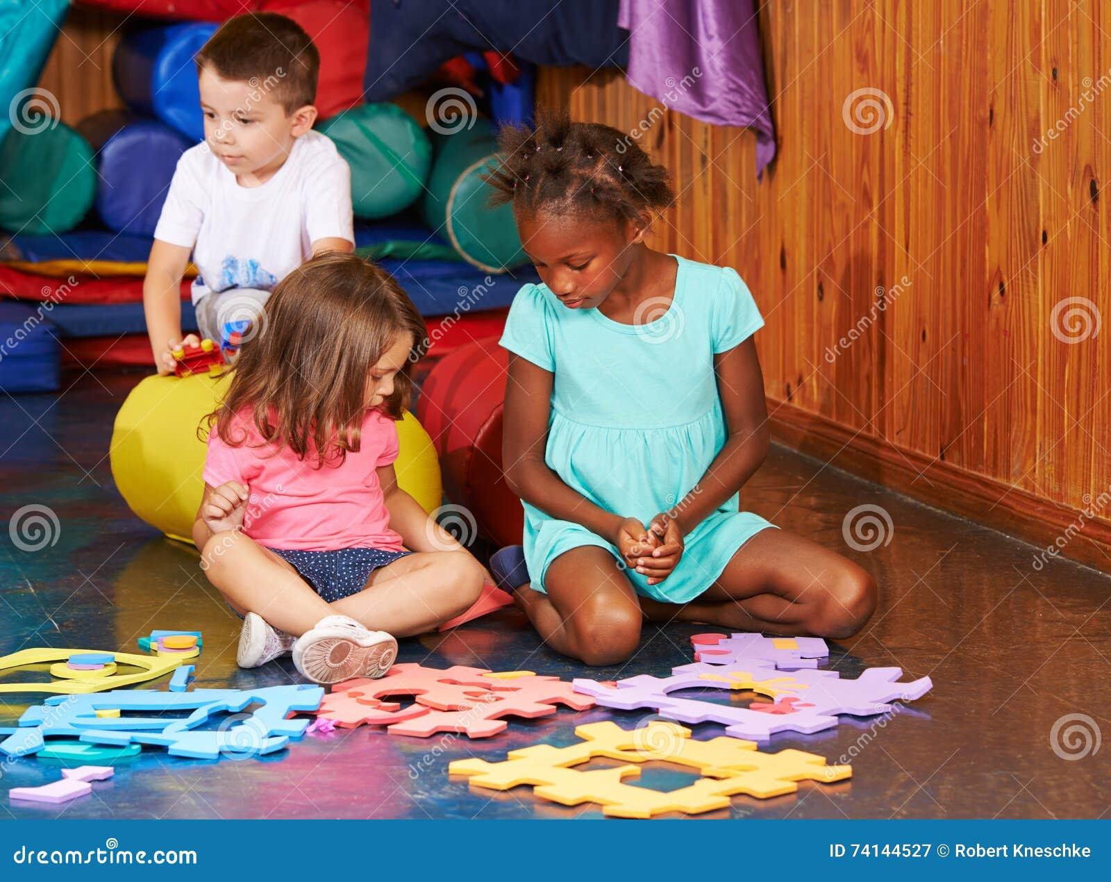 Enfants jouant avec le puzzle denteux dans le jardin d enfants