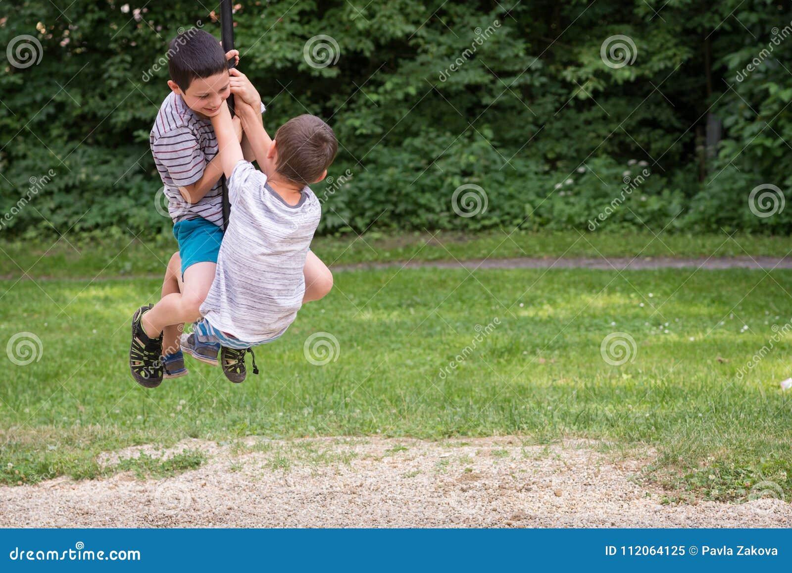 Enfants jouant en parc sur la ligne oscillation de fermeture éclair