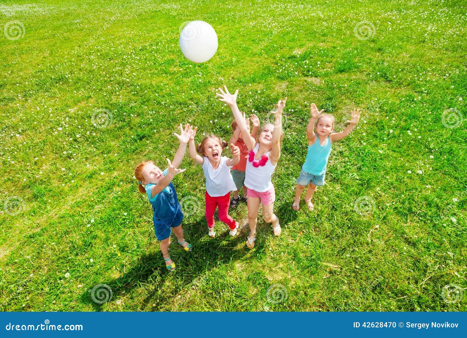 Enfants jouant la boule sur un pré