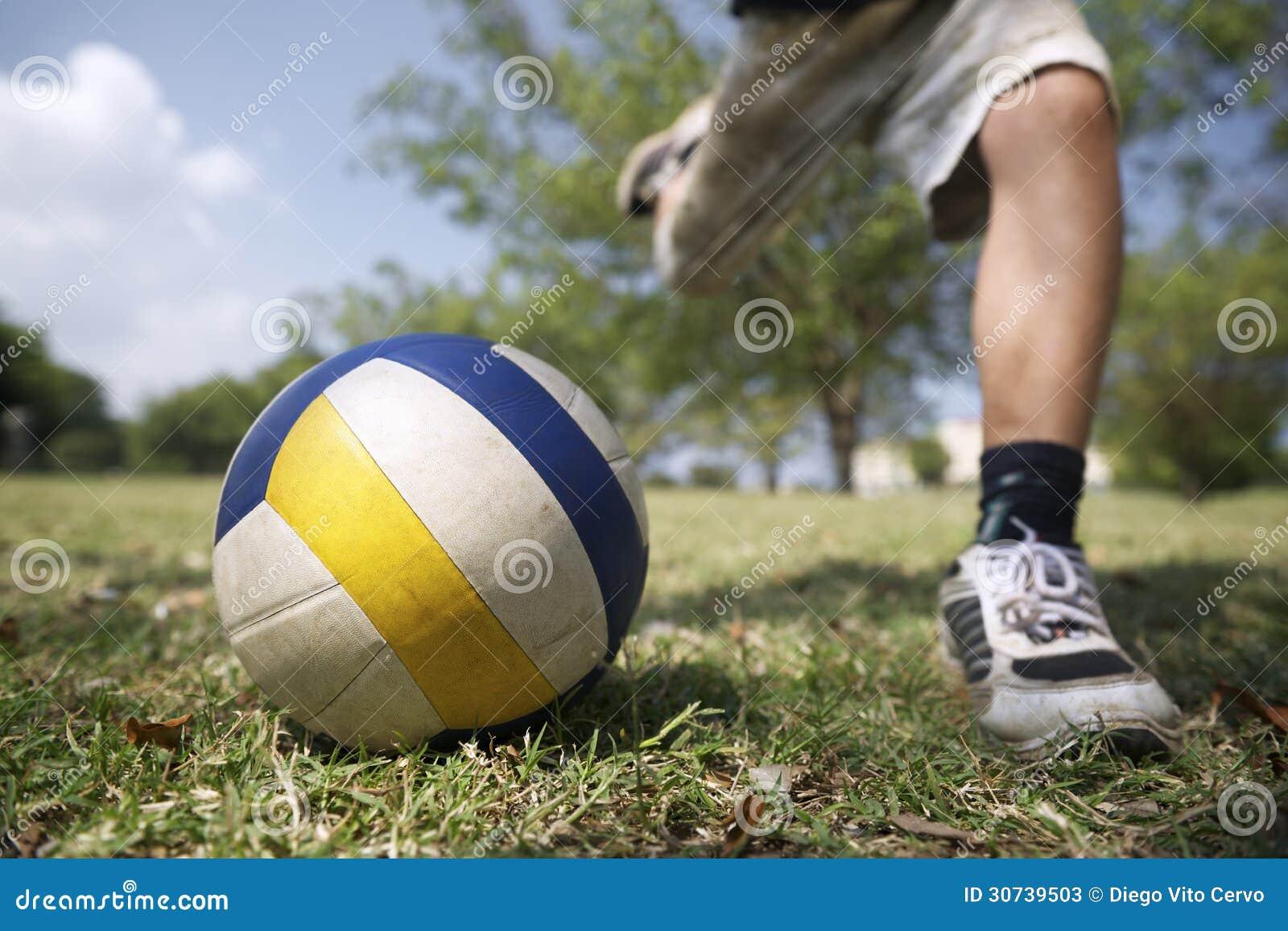 Enfants jouant le jeu de football, jeune garçon frappant la boule en parc