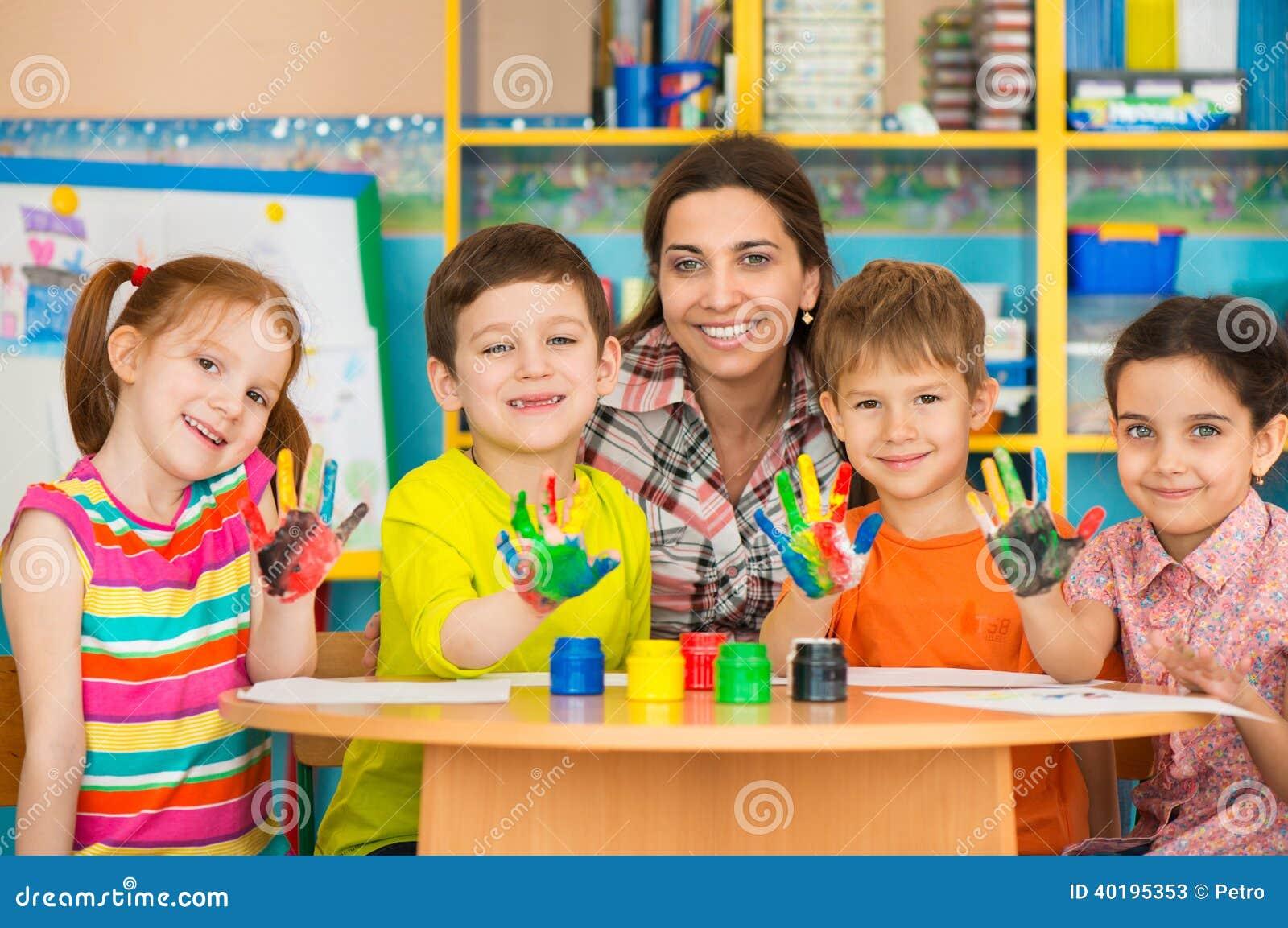 Enfants mignons dessinant avec le professeur à la classe préscolaire