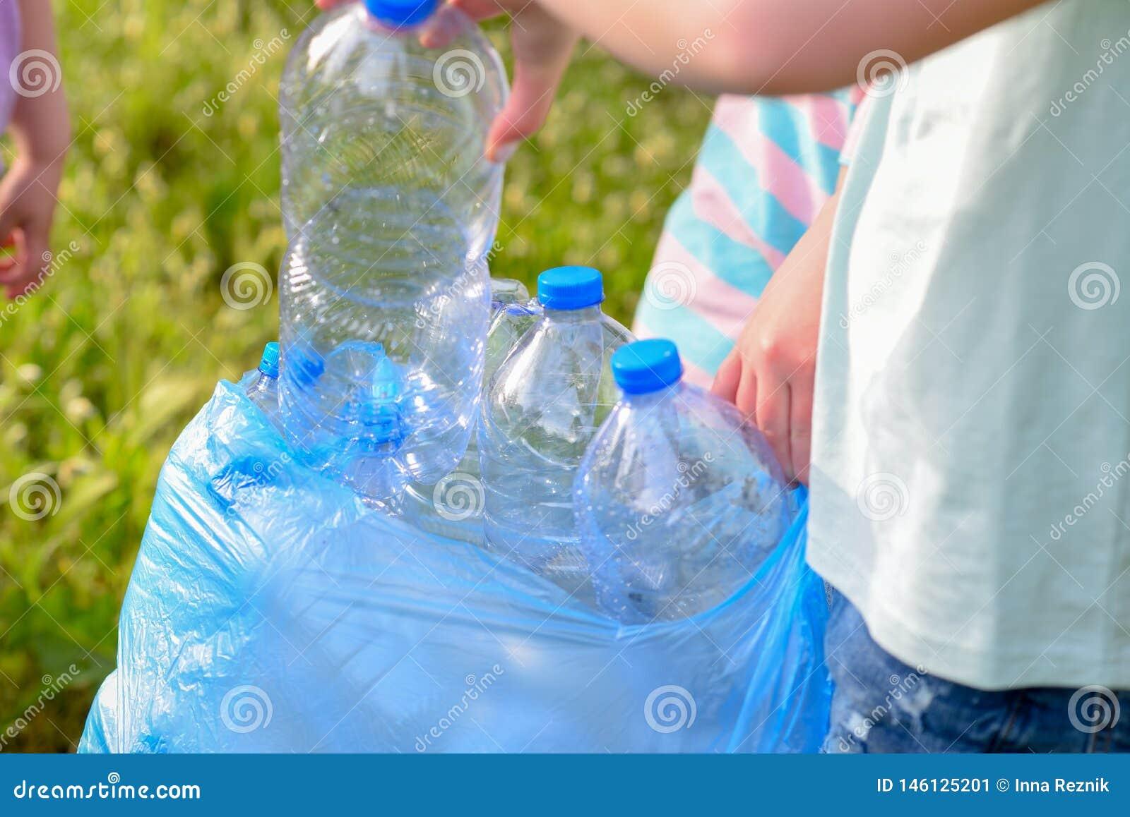 Enfants nettoyant en parc Enfants volontaires avec un sac de déchets nettoyant des ordures, mettant la bouteille en plastique en