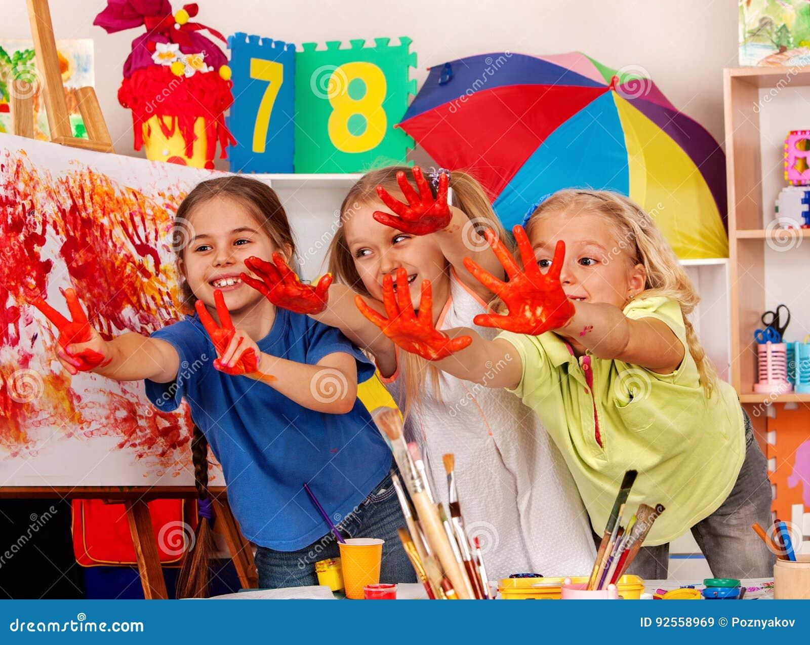 Enfants peignant le doigt sur le chevalet Petits étudiants dans la classe d école d art