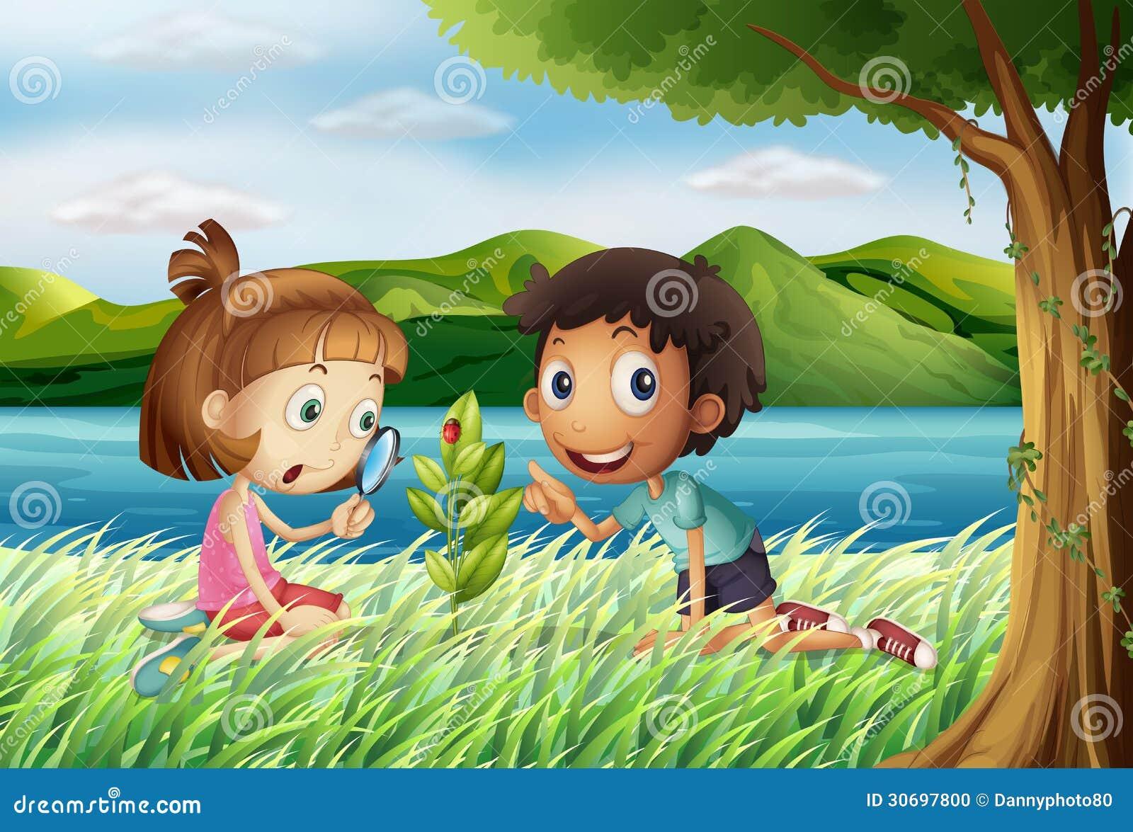 Enfants près de la rivière avec une loupe
