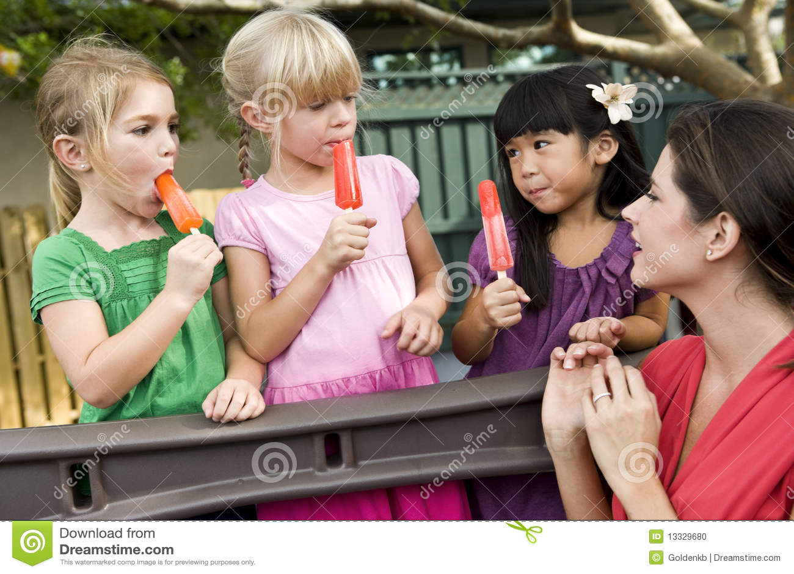 Enfants préscolaires sur la cour de jeu avec le professeur