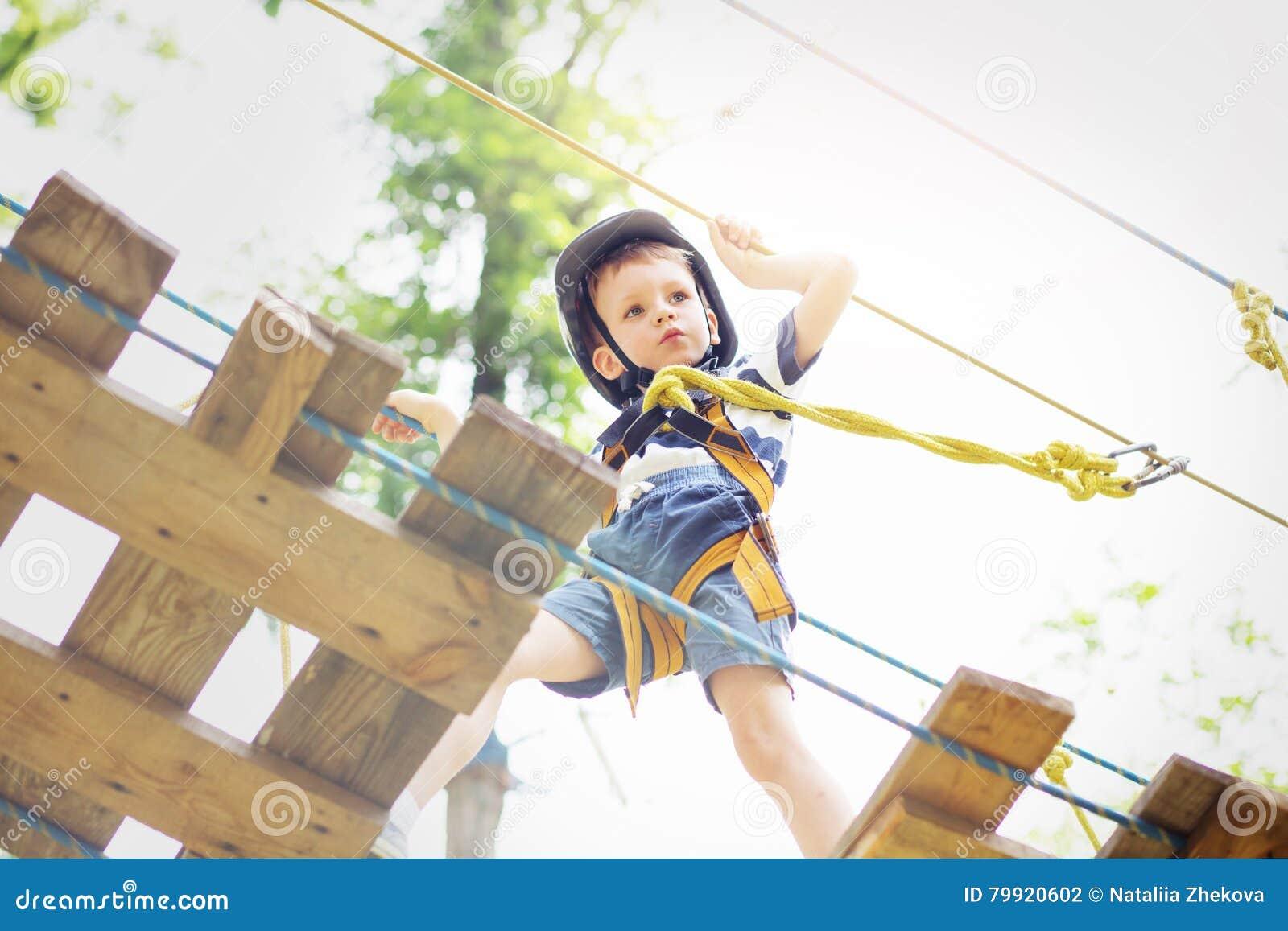 Enfants s élevant en parc d aventure Le garçon a plaisir à s élever dans la corde