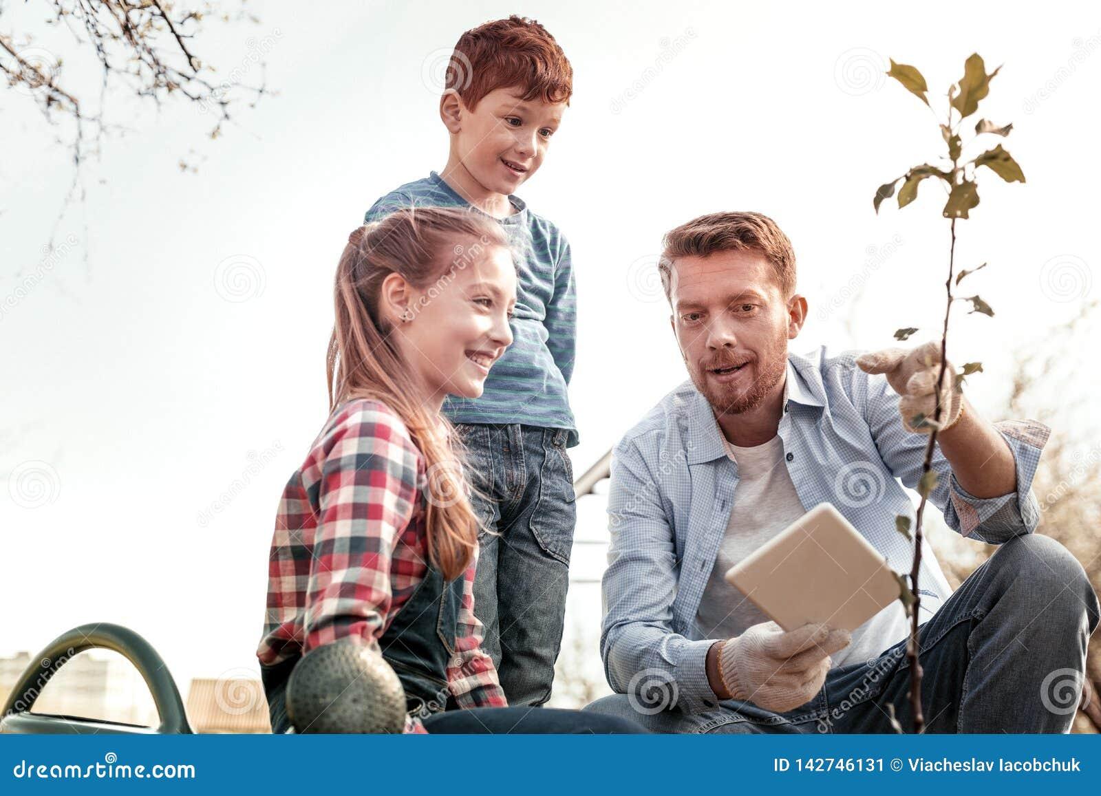 Enfants se demandants souriant tandis que le père expliquent comme l arbre croissant