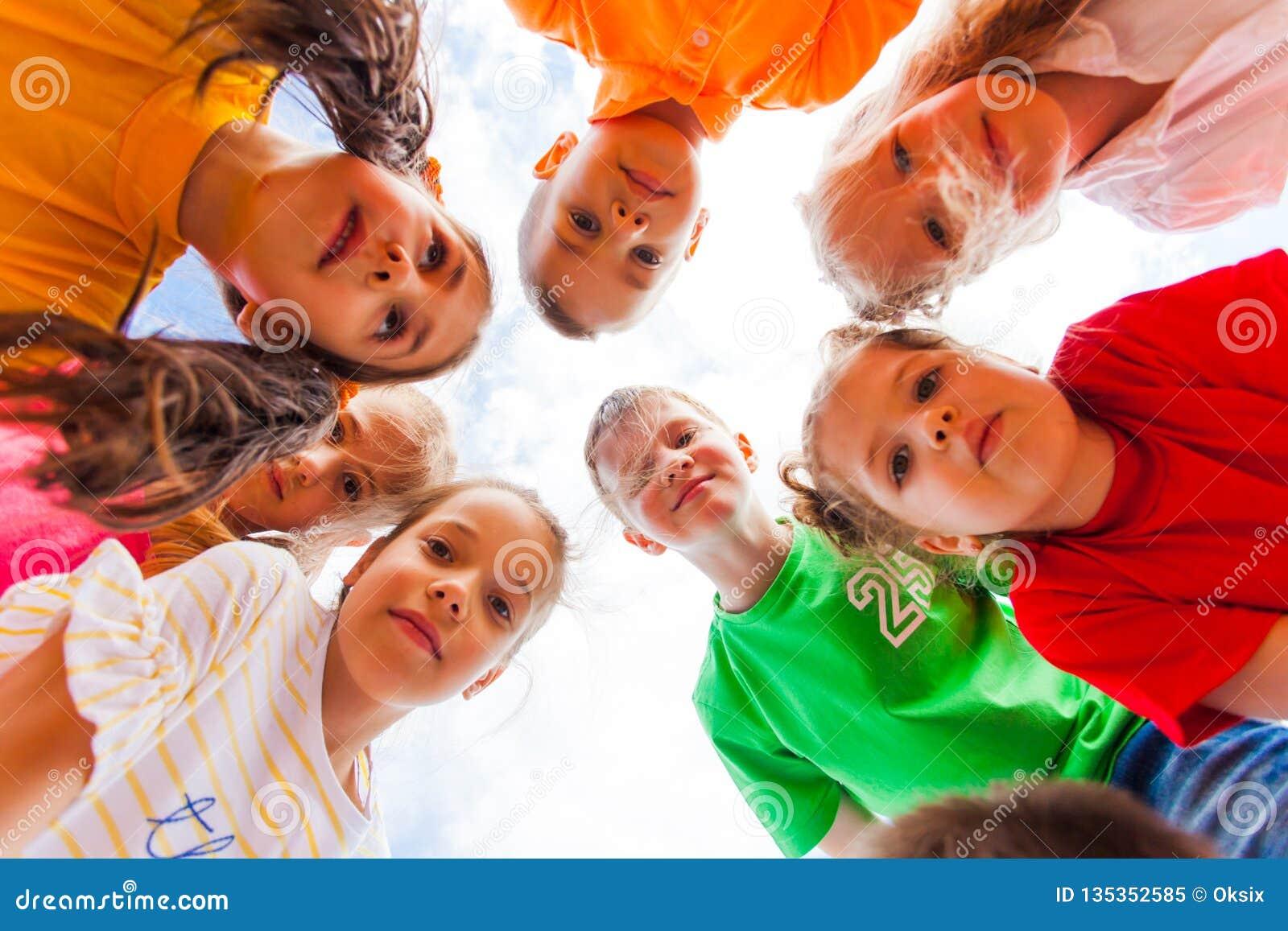 Enfants se tenant ensemble en cercle regardant la caméra