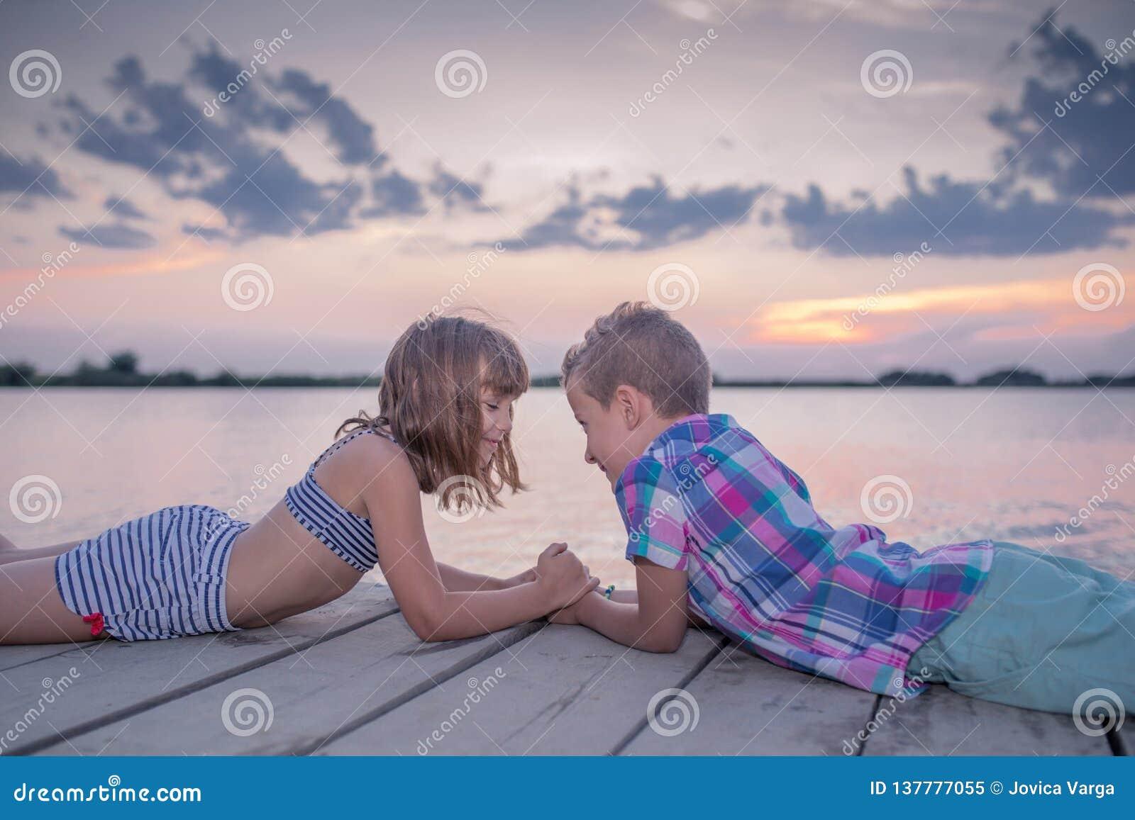 Enfants se trouvant par la rivière et tenant des mains