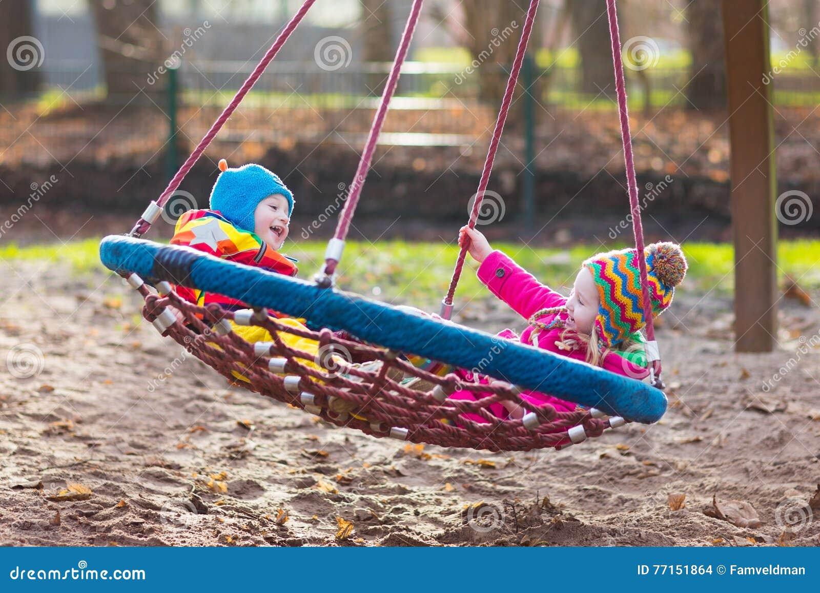 Enfants sur l oscillation de terrain de jeu