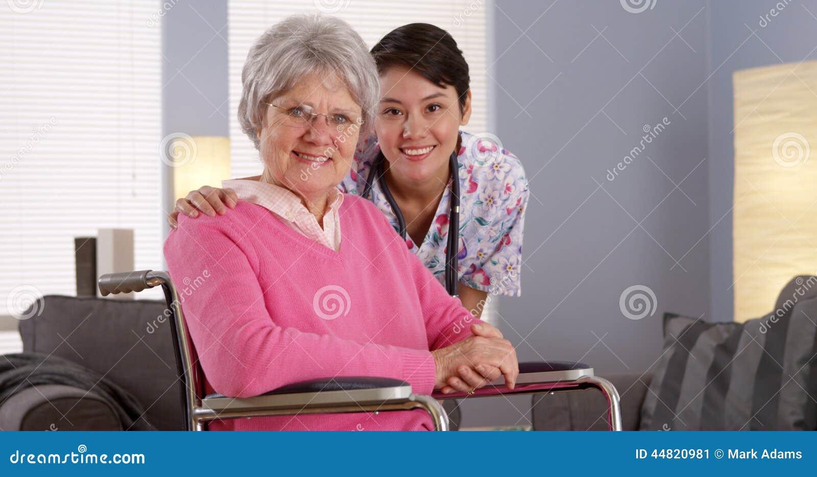 Enfermeira asiática que sorri com paciente idoso