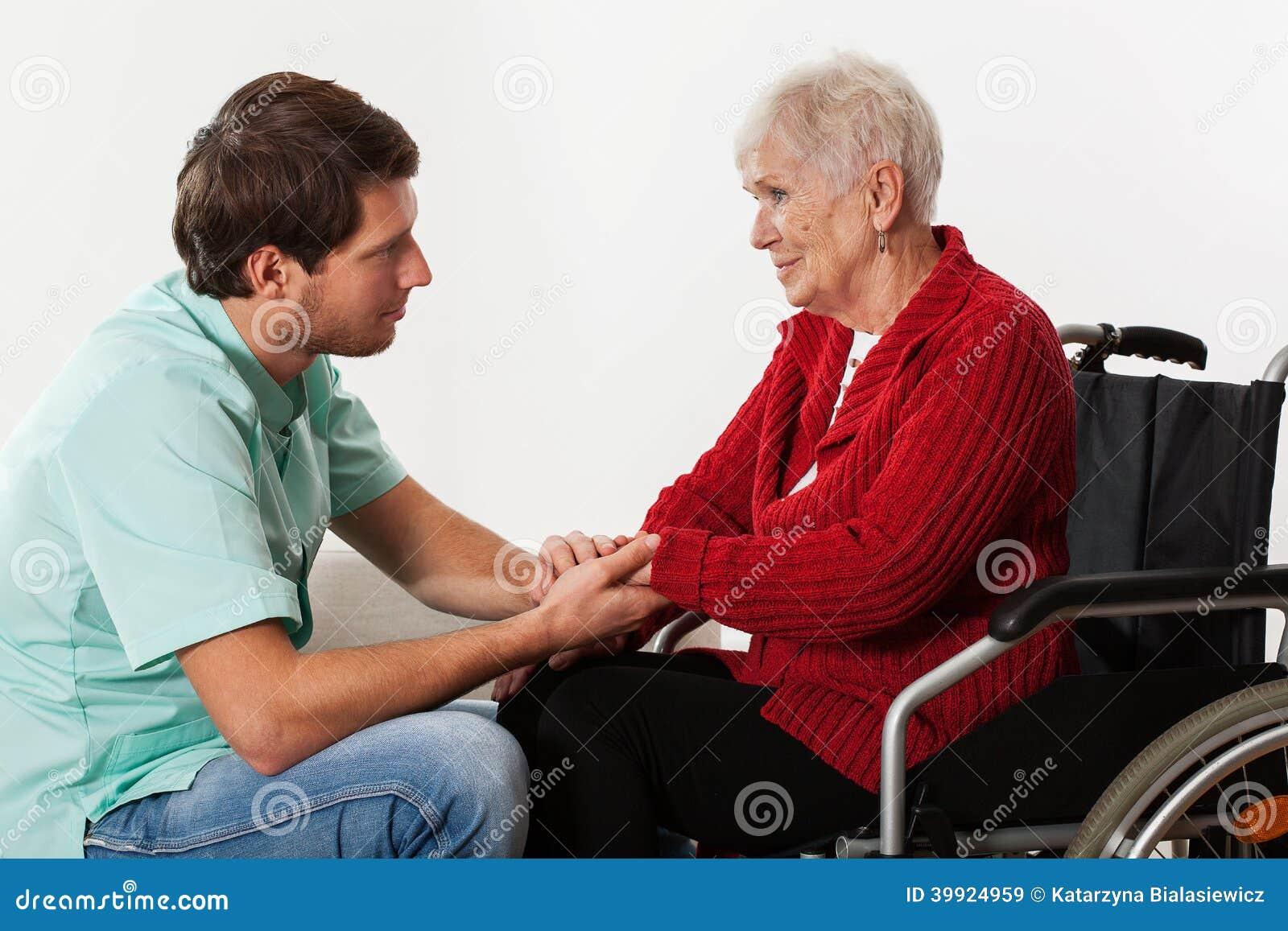 Enfermeira dos jovens que ajuda à senhora deficiente