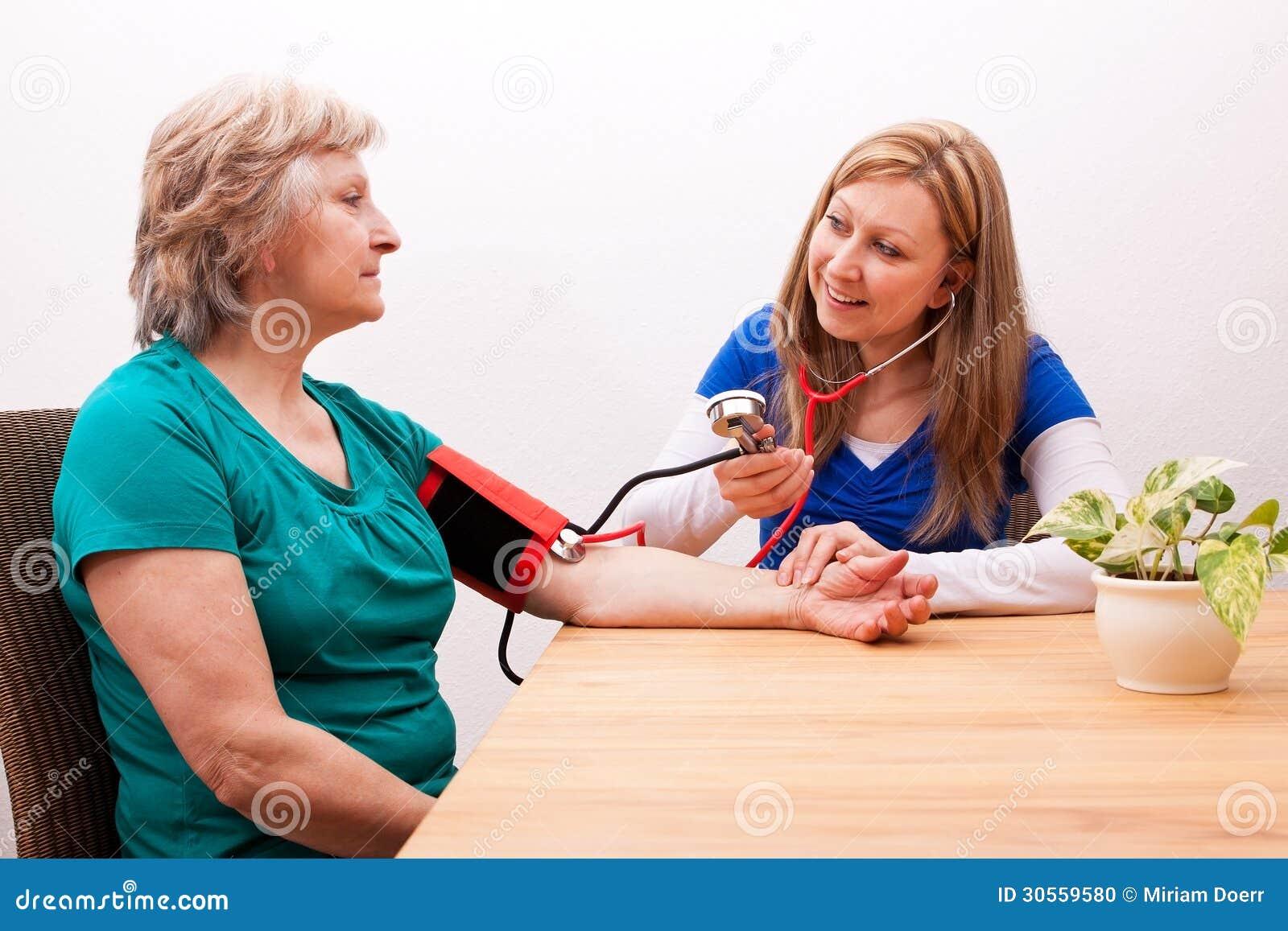 A enfermeira mede o sênior a pressão sanguínea