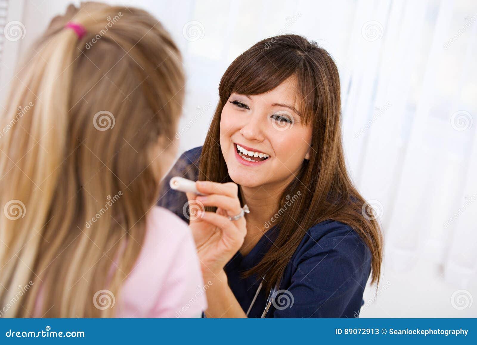 Enfermeira: Olhando uma garganta do ` s da criança