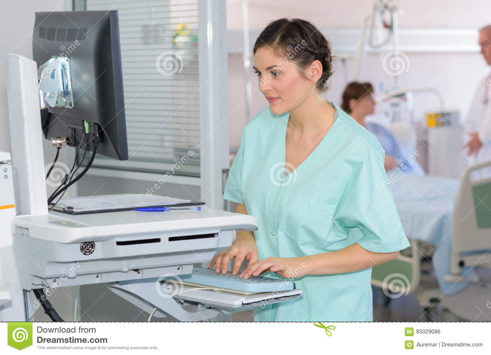 Enfermeira que olha raios X no tela de computador