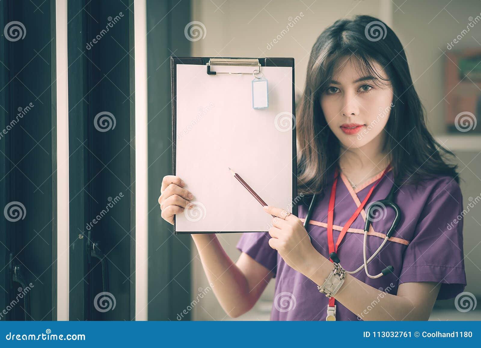 Enfermera de sexo femenino joven que sostiene el lápiz y que muestra su tablero