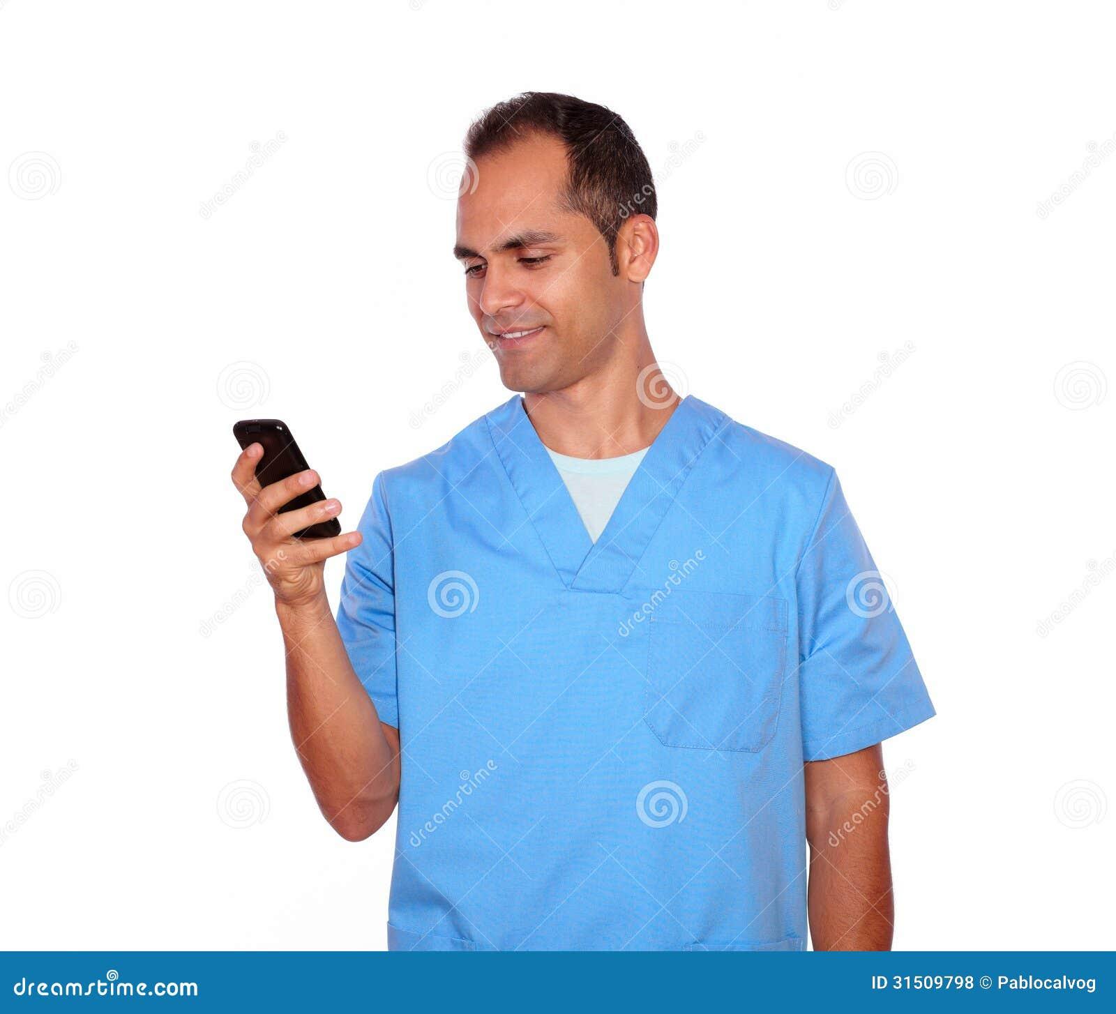 Enfermera de sexo masculino sonriente que envía el mensaje en el teléfono móvil