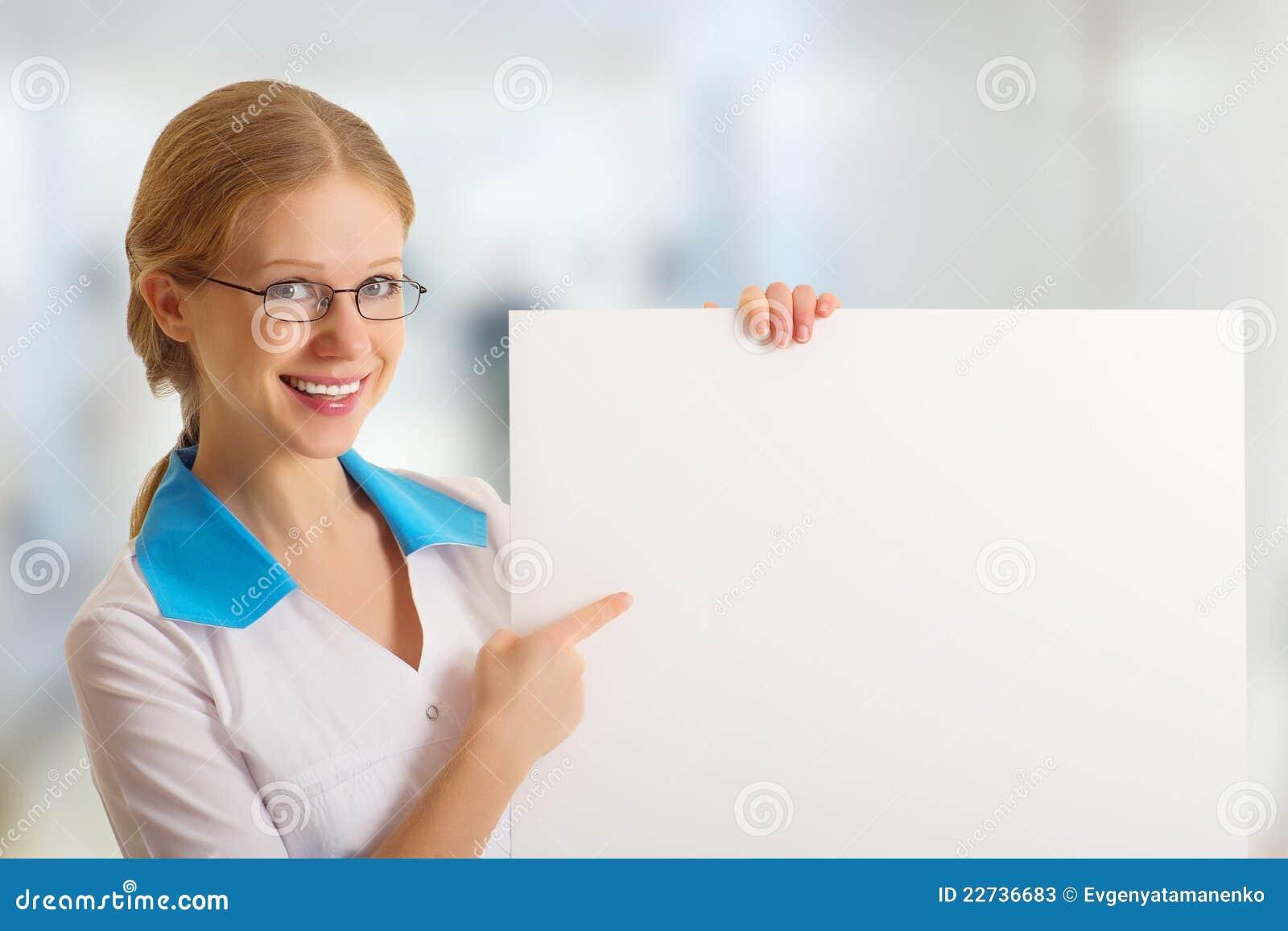 Enfermera hermosa que sostiene una cartelera en blanco