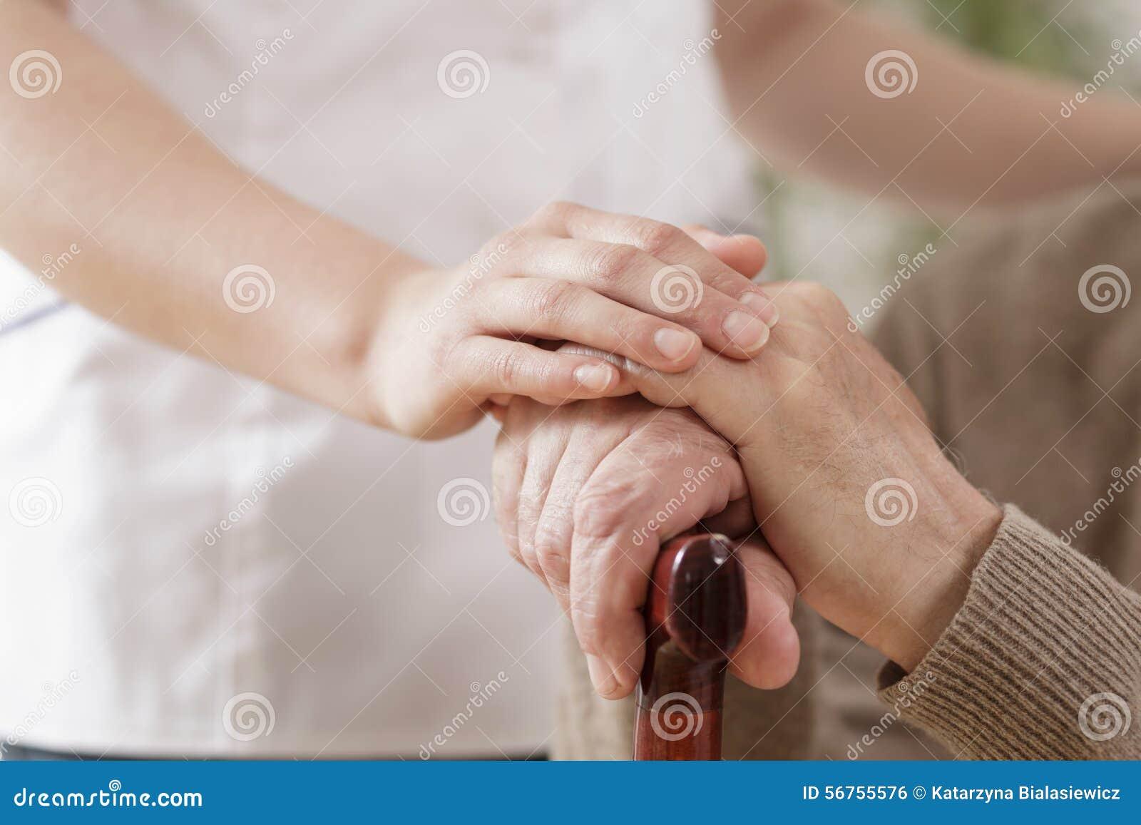 Enfermera que ayuda al más viejo hombre enfermo