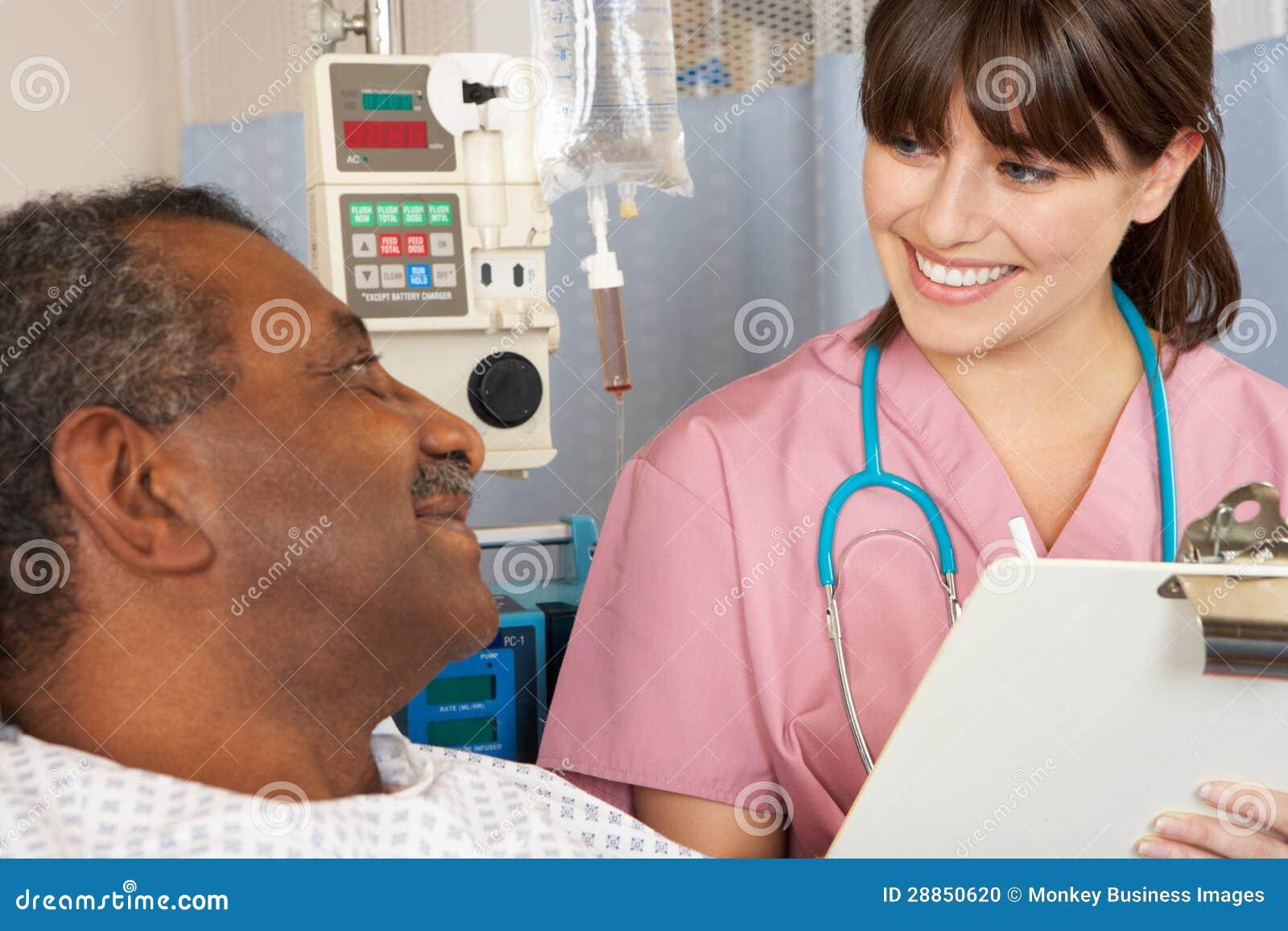 Enfermera que habla con el paciente masculino mayor en sala