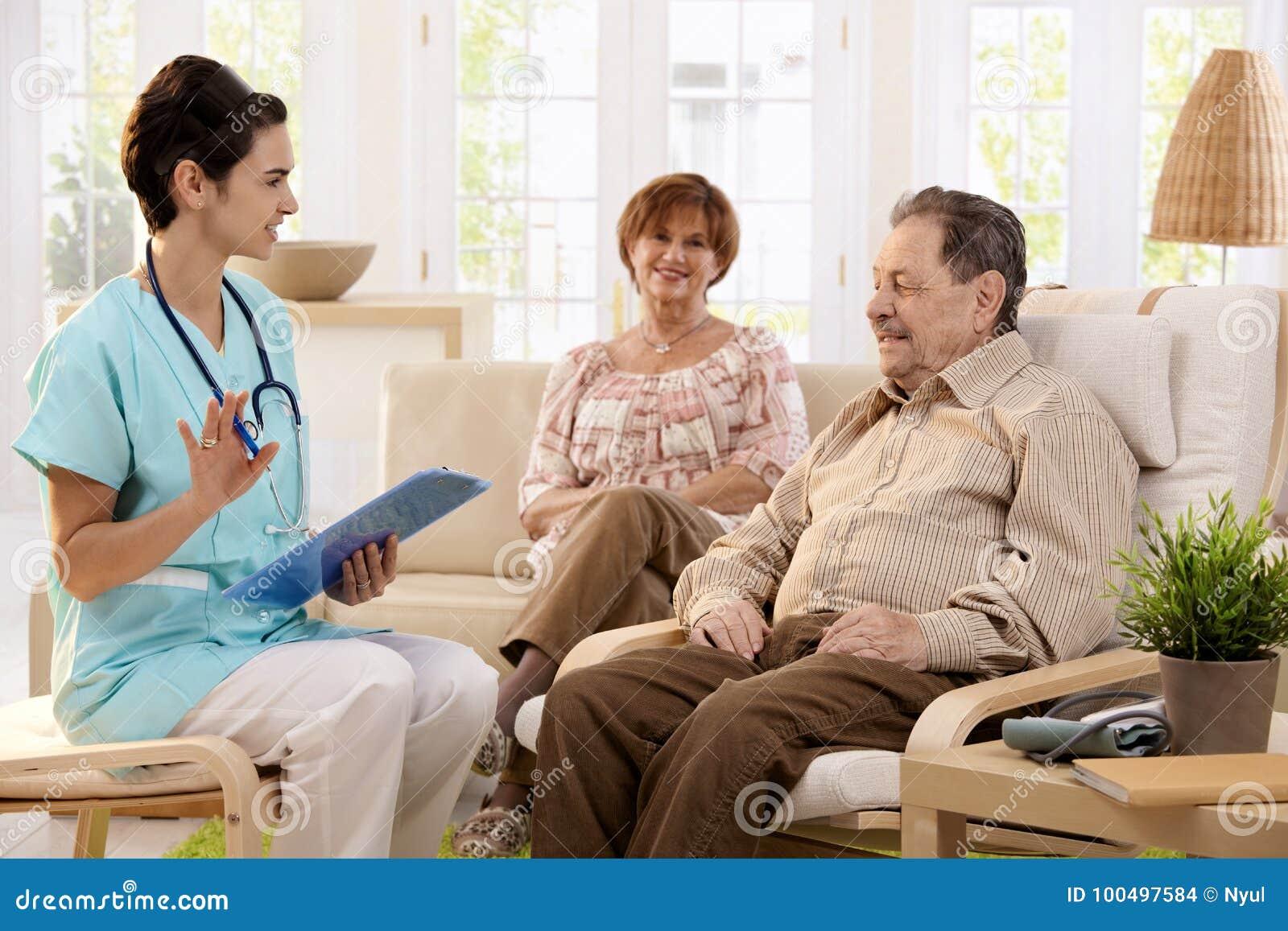 Enfermera que habla con los pacientes mayores en casa