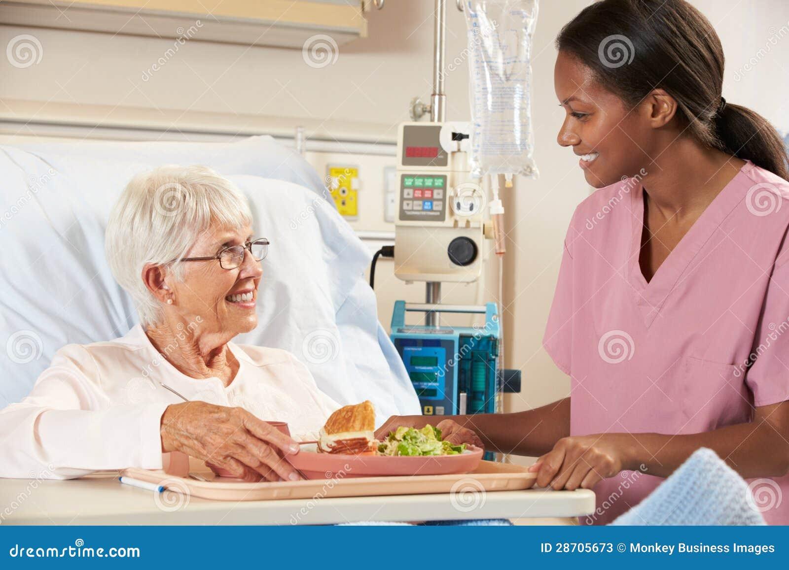 Enfermera Que Sirve La Comida Paciente Femenina Mayor En Cama De Hospital Fotos de archivo ...
