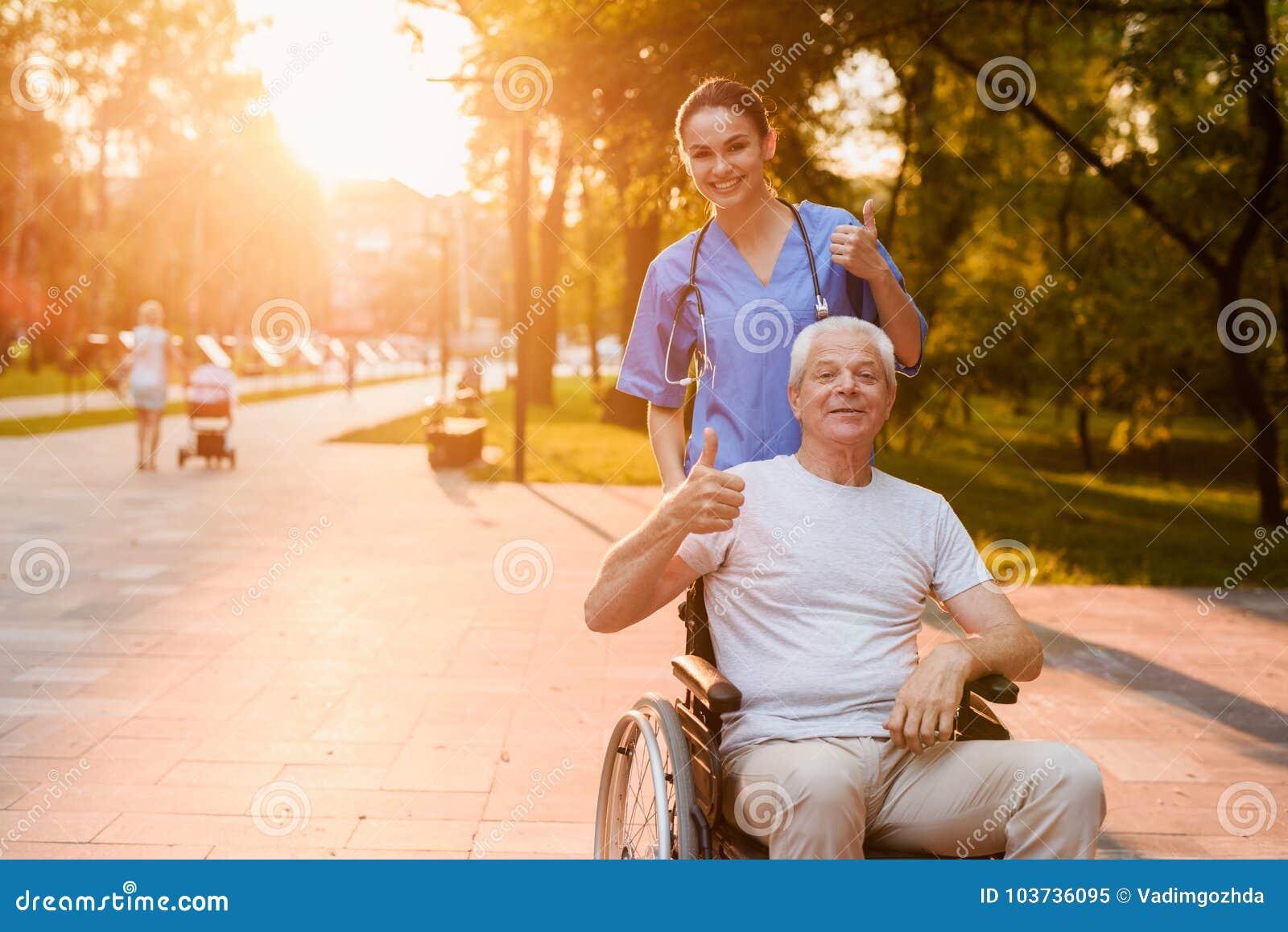 Enfermera y viejo hombre que sienta en mostrar de la silla de ruedas los pulgares para arriba en el parque en la puesta del sol