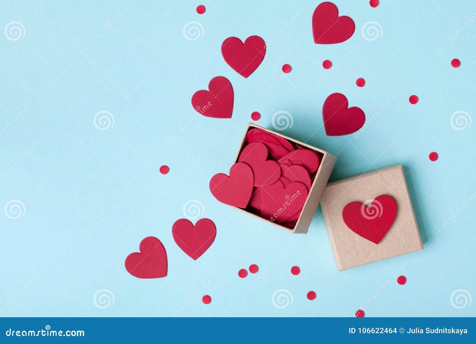 Enfermez dans une boîte complètement des coeurs et des confettis rouges sur la vue supérieure bleue de table Fond de jour de vale